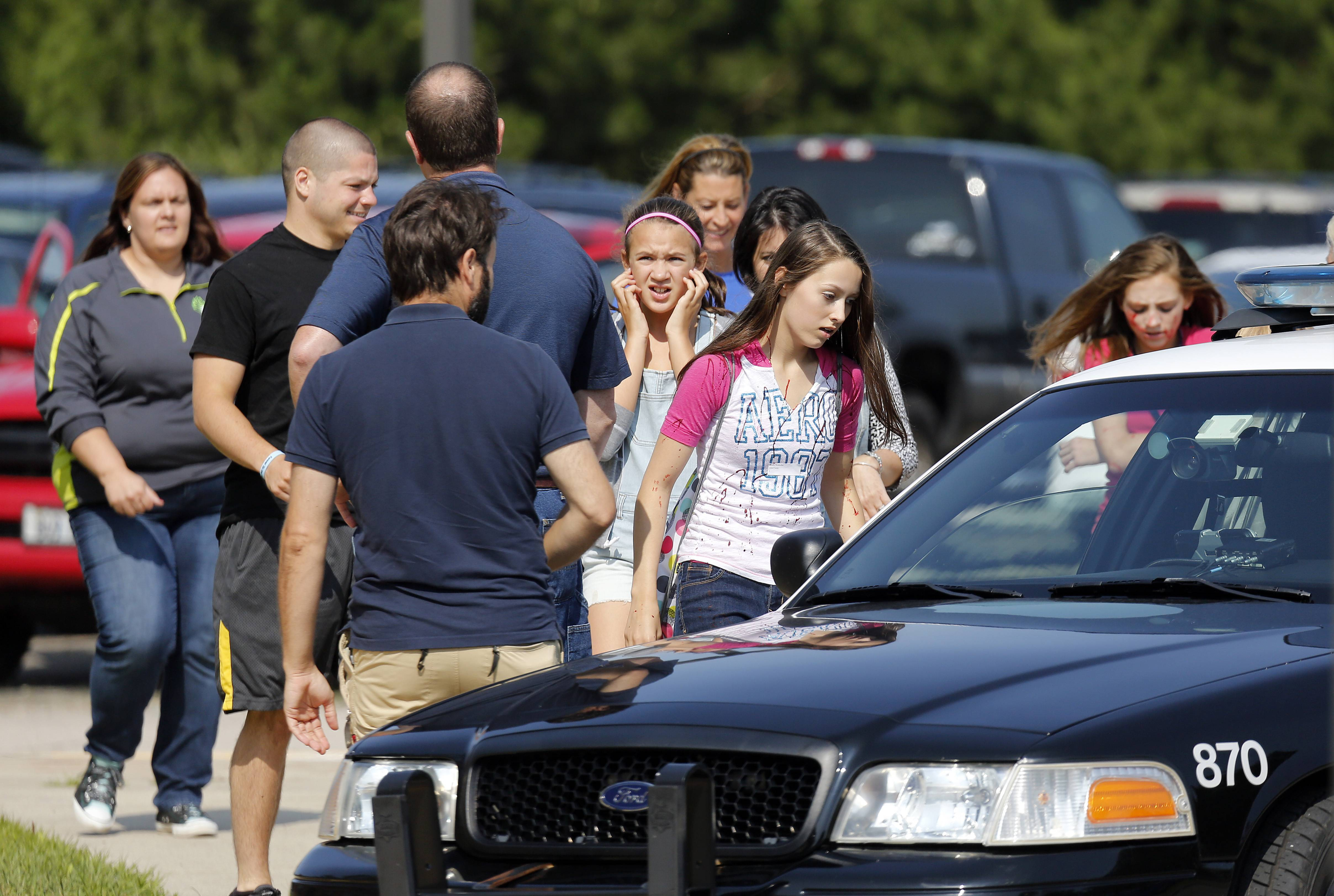 Fake victims are evacuated Thursday morning to the parking lot of Otter Creek Elementary School in Elgin. The training included a shooter who killed seven people and injured 47.