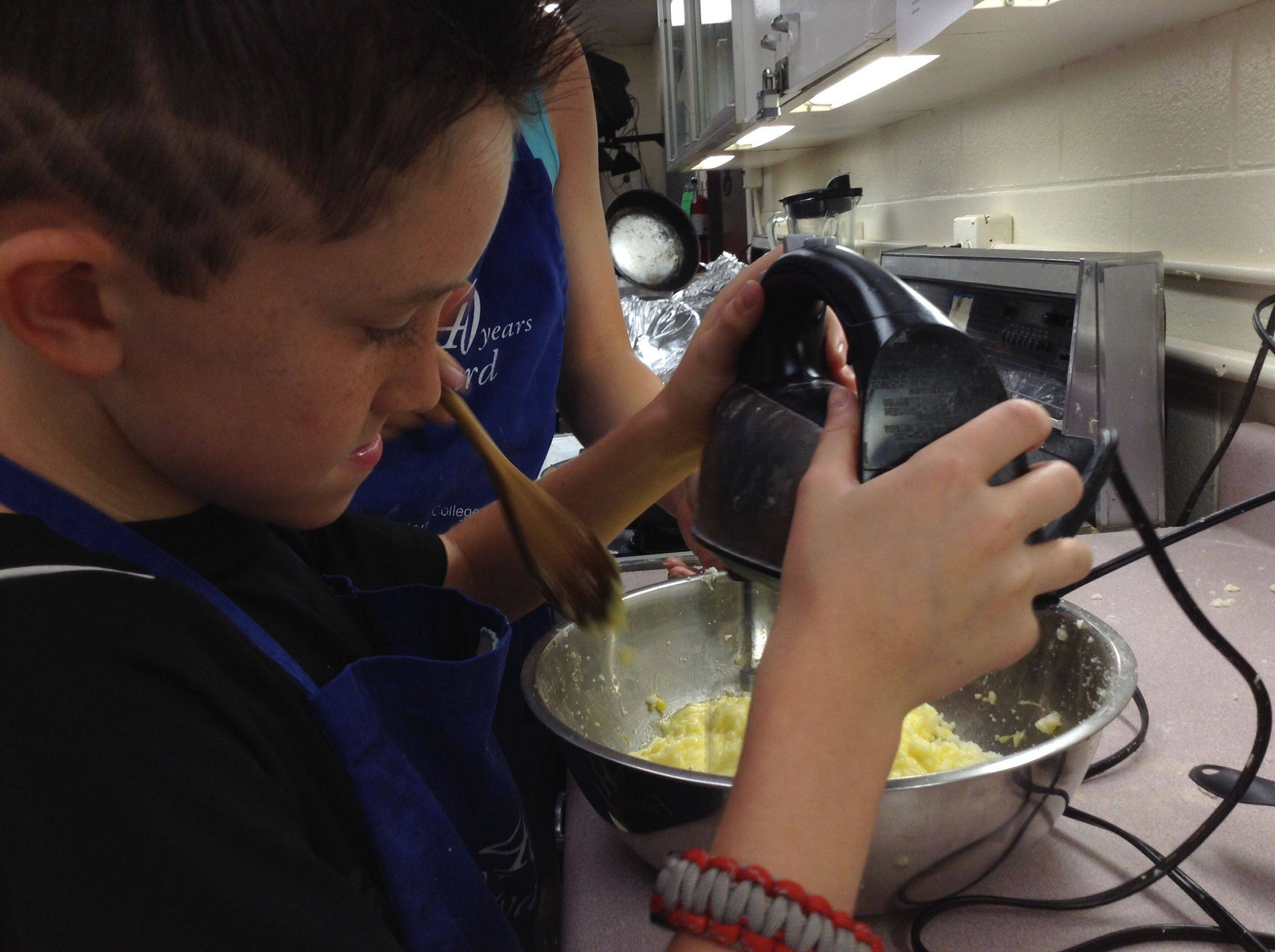 Josh King, 11, mixes sugar and butter during a Harper College summer culinary class. His cookies will wrap up a lunch for homeless families Thursday.
