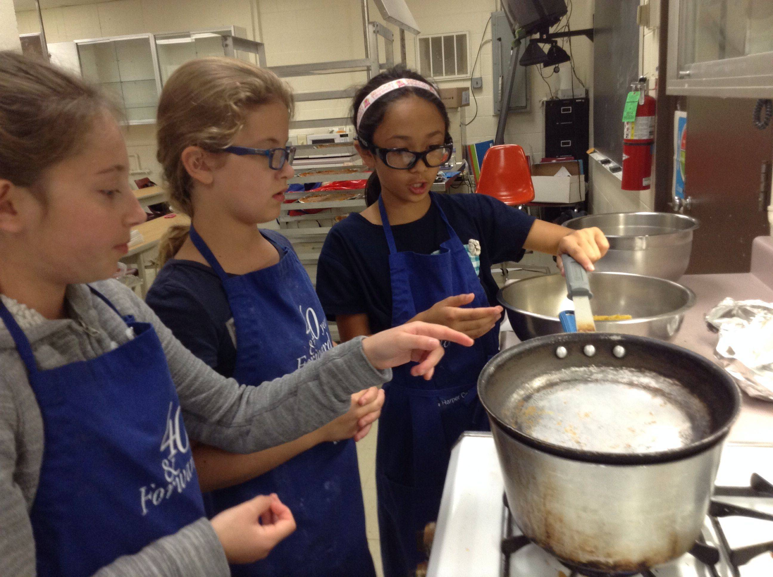 Mati Ciprian, 12, of Bloomingdale, Izabella Filip, 11, of Inverness, and Ananya Gupta, 10, of Roselle, prepare to boil water for penne pasta.
