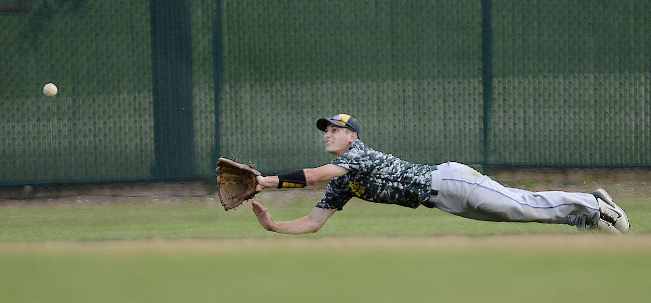 Crystal Lake's Michael Avella dives in left field for a ball hit by Batavia's Michael Fossali in the championship game of the St. Charles East regional. The ball got past Avella for a double.