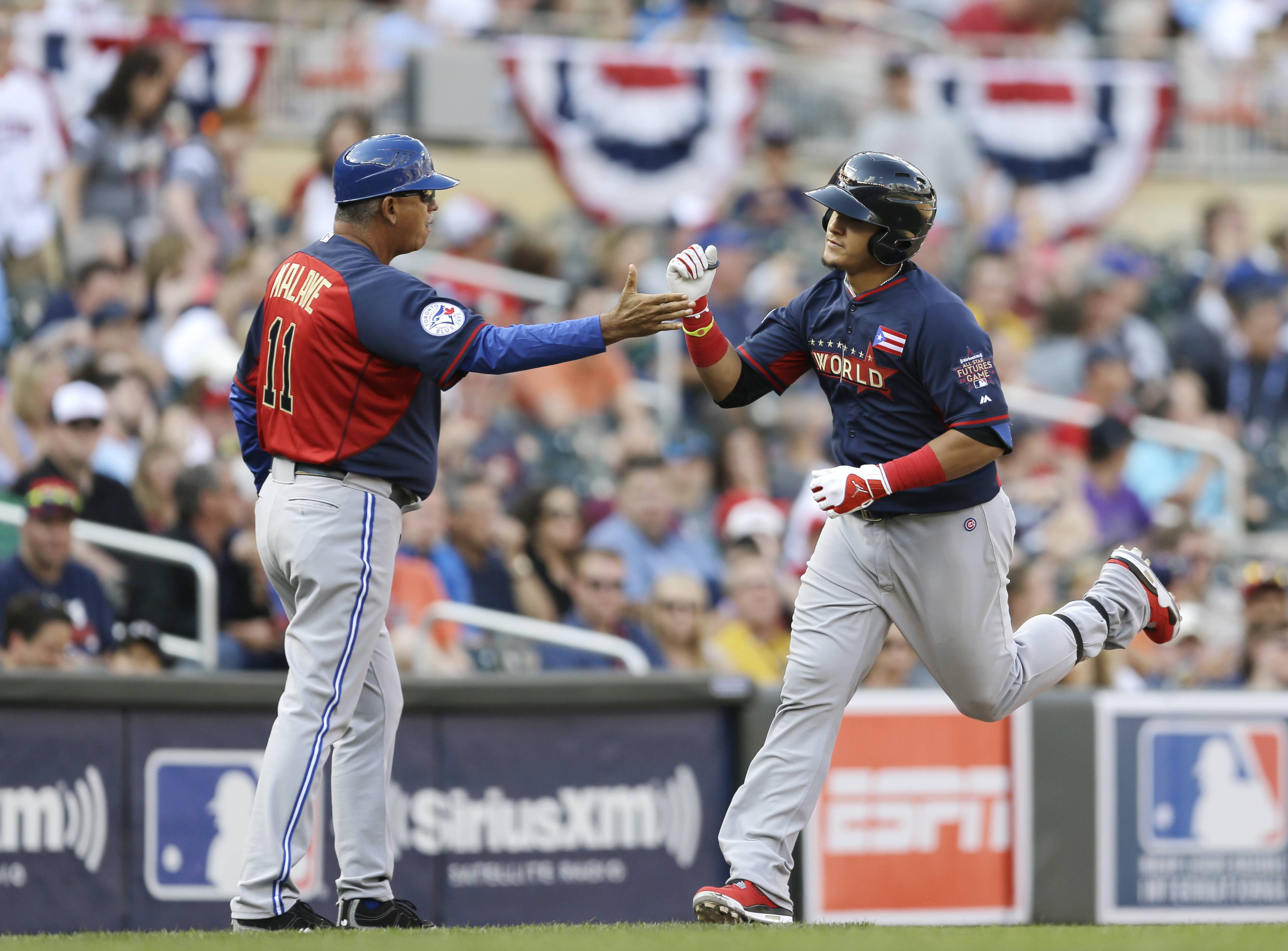 Cubs prospect Javier Baez, right, is greeted by third base coach Omar Malave, left, after hitting a two-run home run for the Worlds in the sixth inning of the All-Star Futures baseball game against the United States, Sunday, July 13, 2014, in Minneapolis.