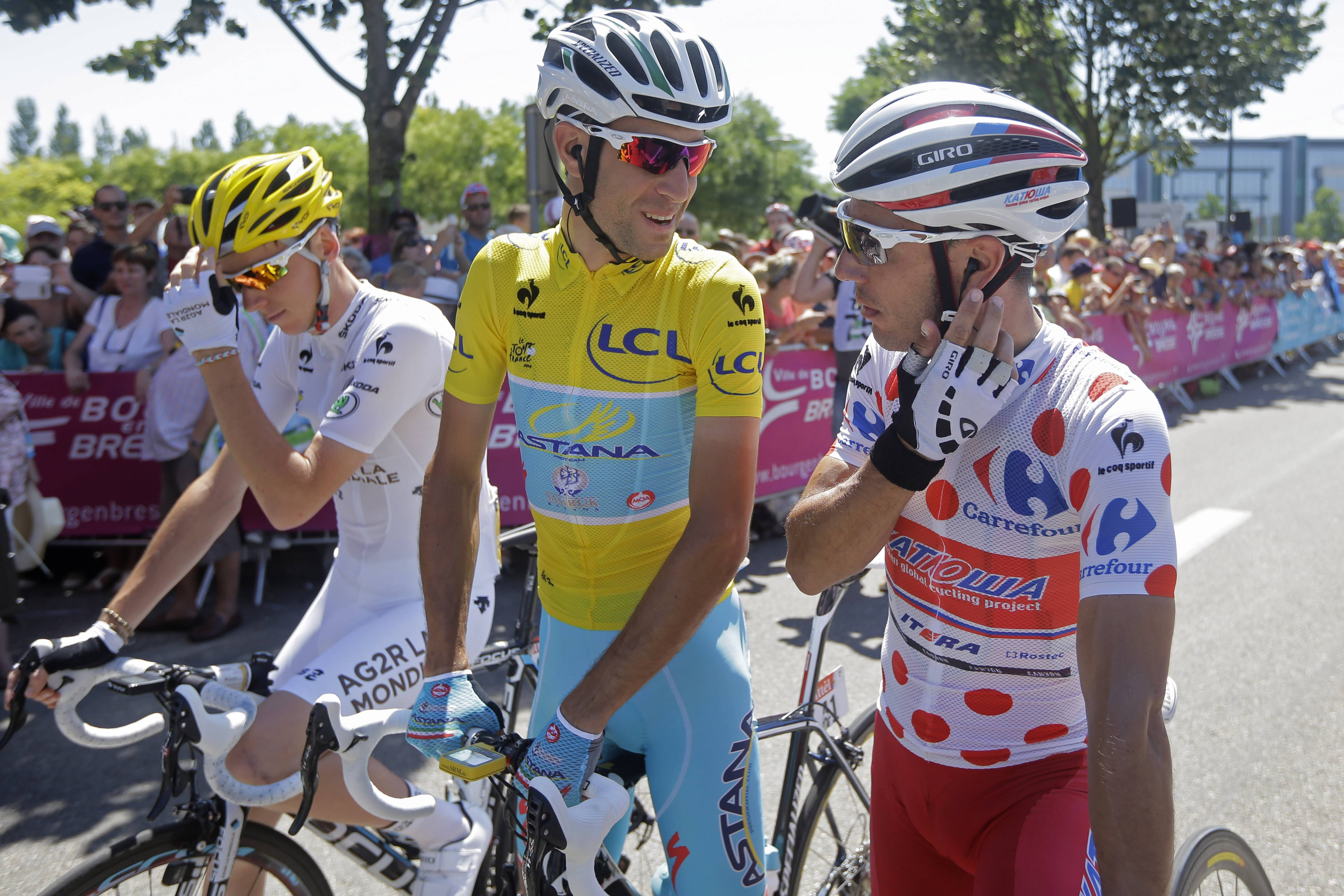 Italy's Vincenzo Nibali, wearing the overall leader's yellow jersey, talks to Spain's Joaquim Rodriguez, wearing the best climber's dotted jersey, as they wait Thursday with France's Romain Bardet, wearing the best young rider's white jersey, for the start of the twelfth stage of the Tour de France.