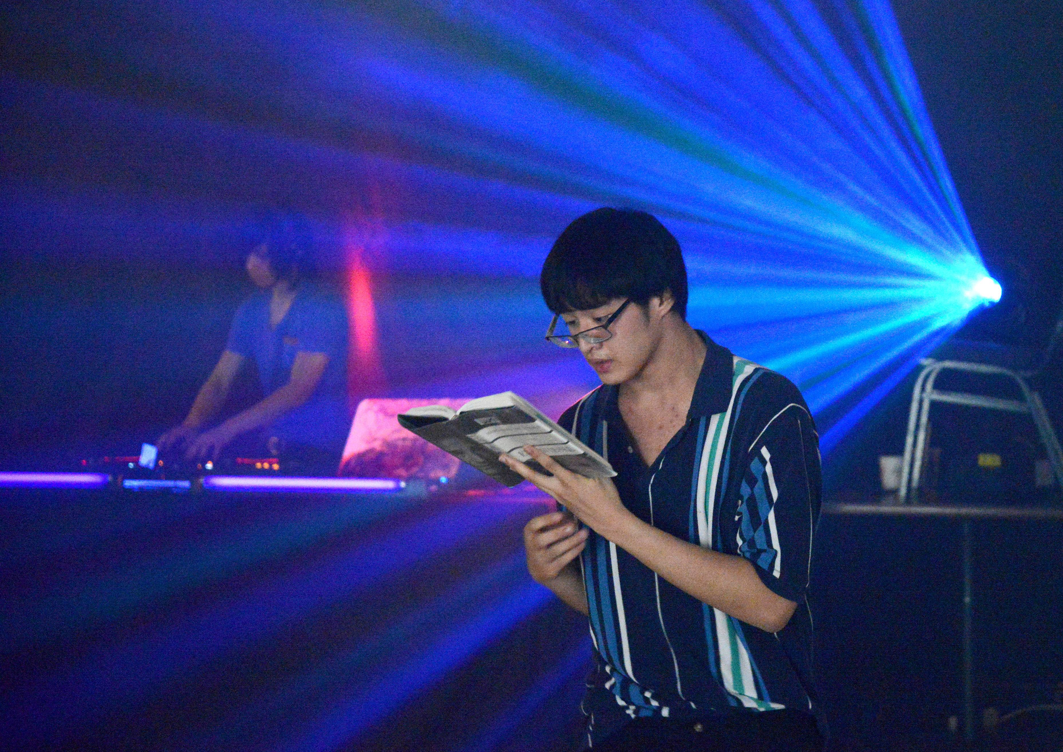 "Justin Habana, 17, of Elgin reads, ""Dawn,"" by Elie Wiesel while he simultaneously dances at the Teen Writers and Artists Project's T-WAAP Sock Hop dance marathon Friday at The Quad/Charlestowne Mall in St. Charles. The nonprofit organization held the event to raise funds to keep the organization running and create more events."