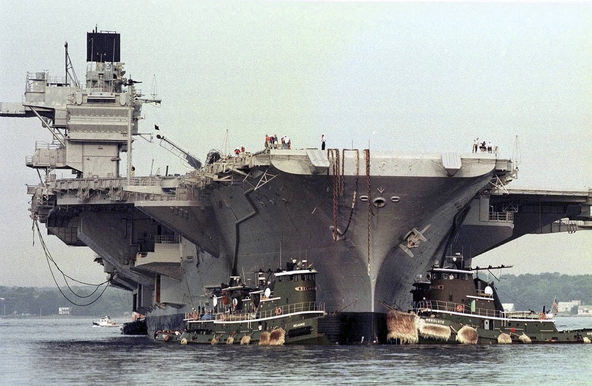 The U.S.S. Saratoga aircraft carrier is guided into Pier One of Coddington Cove in Middletown, R.I., by tugs after a five-day journey from the Philadelphia Naval Yard.