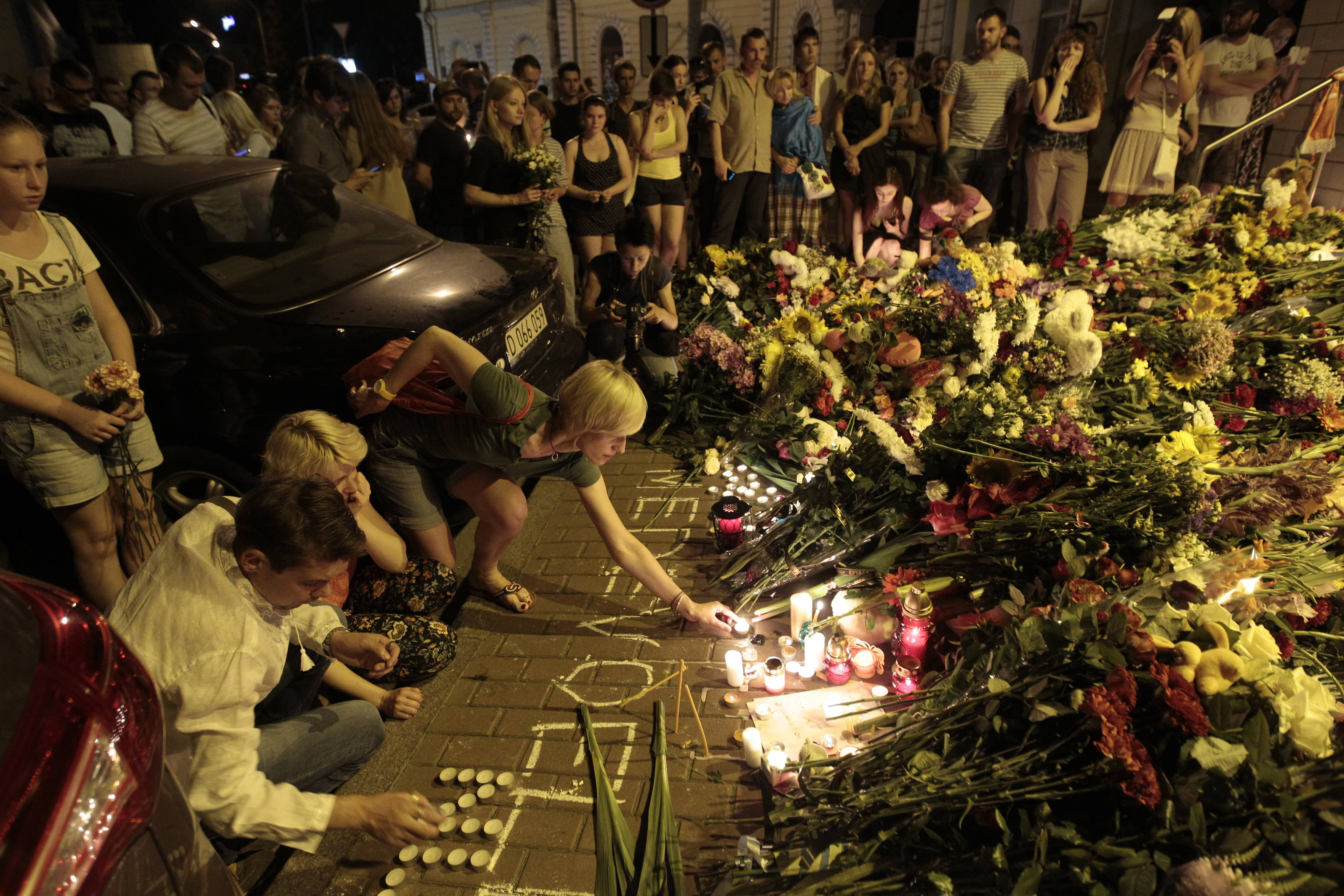People hold candles and place flower tributes Thursday outside the Dutch embassy to commemorate victims of Malaysia Airlines plane crash in Kiev, Ukraine. A Malaysian Airlines passenger jet was shot down in eastern Ukraine on Thursday, and both the Ukrainian government and pro-Russian rebels blamed one another for the attack.