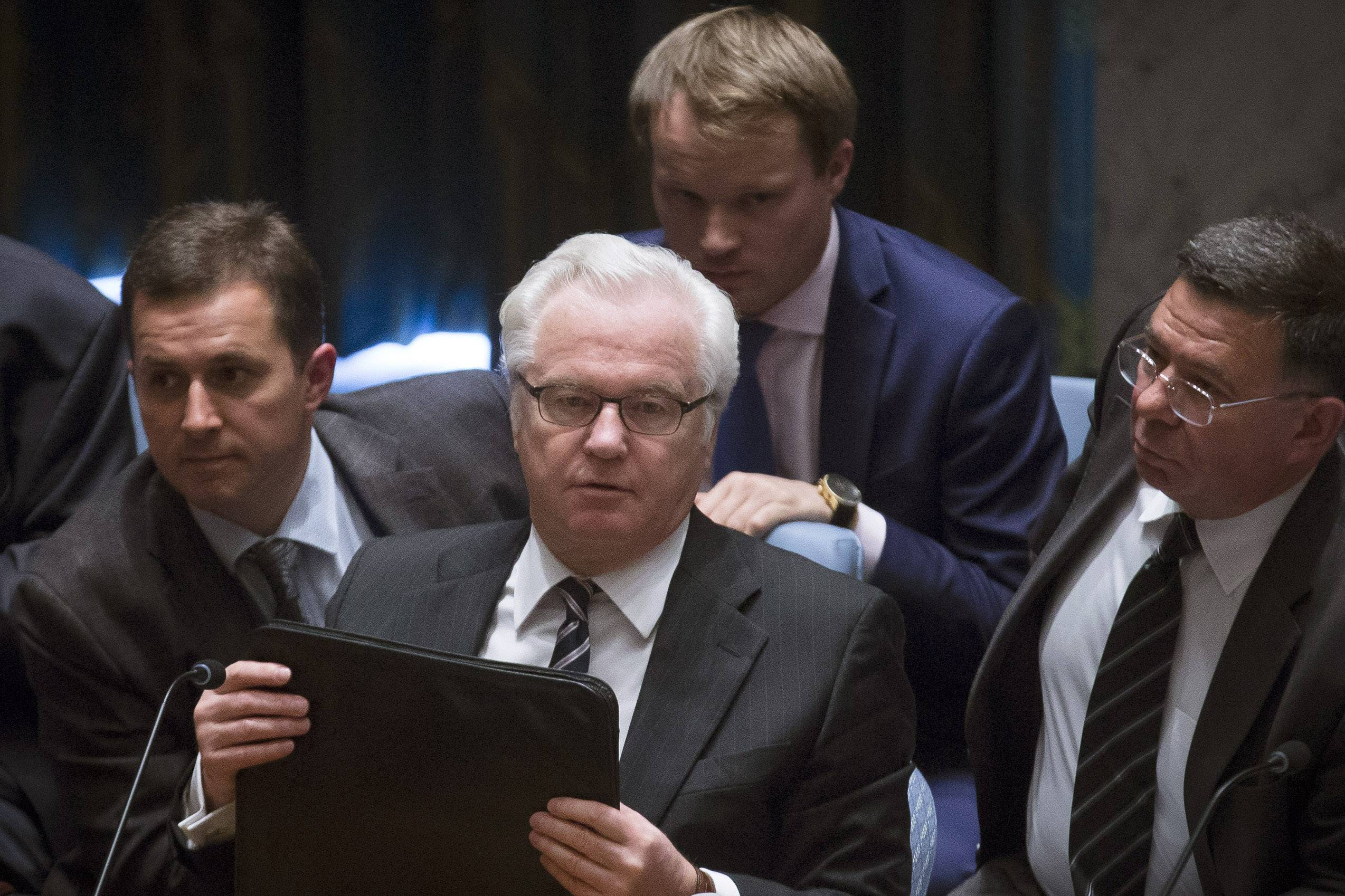 Russian U.N. Ambassador Vitaly Churkin, center, prepares to leave following a U.N. Security Council meeting at United Nations headquarters Friday. Britain's U.N. Mission says it requested an emergency meeting after Thursday's downing of a Malaysia Airlines plane carrying 298 people over eastern Ukraine.