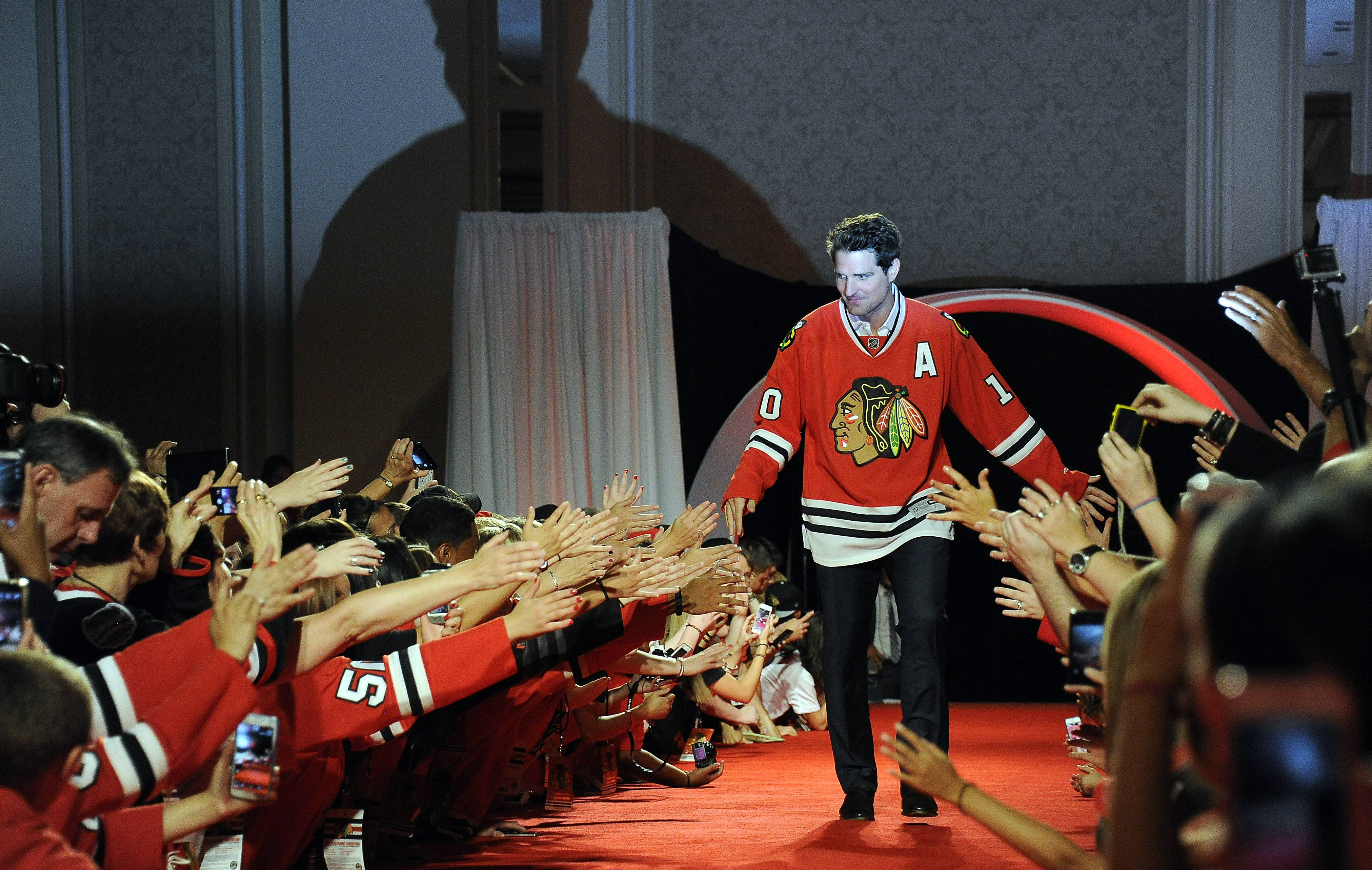 The Blackhawks' Patrick Sharp walks the red carpet as fans cheer at the seventh annual Blackhawks Convention in Chicago on Friday.