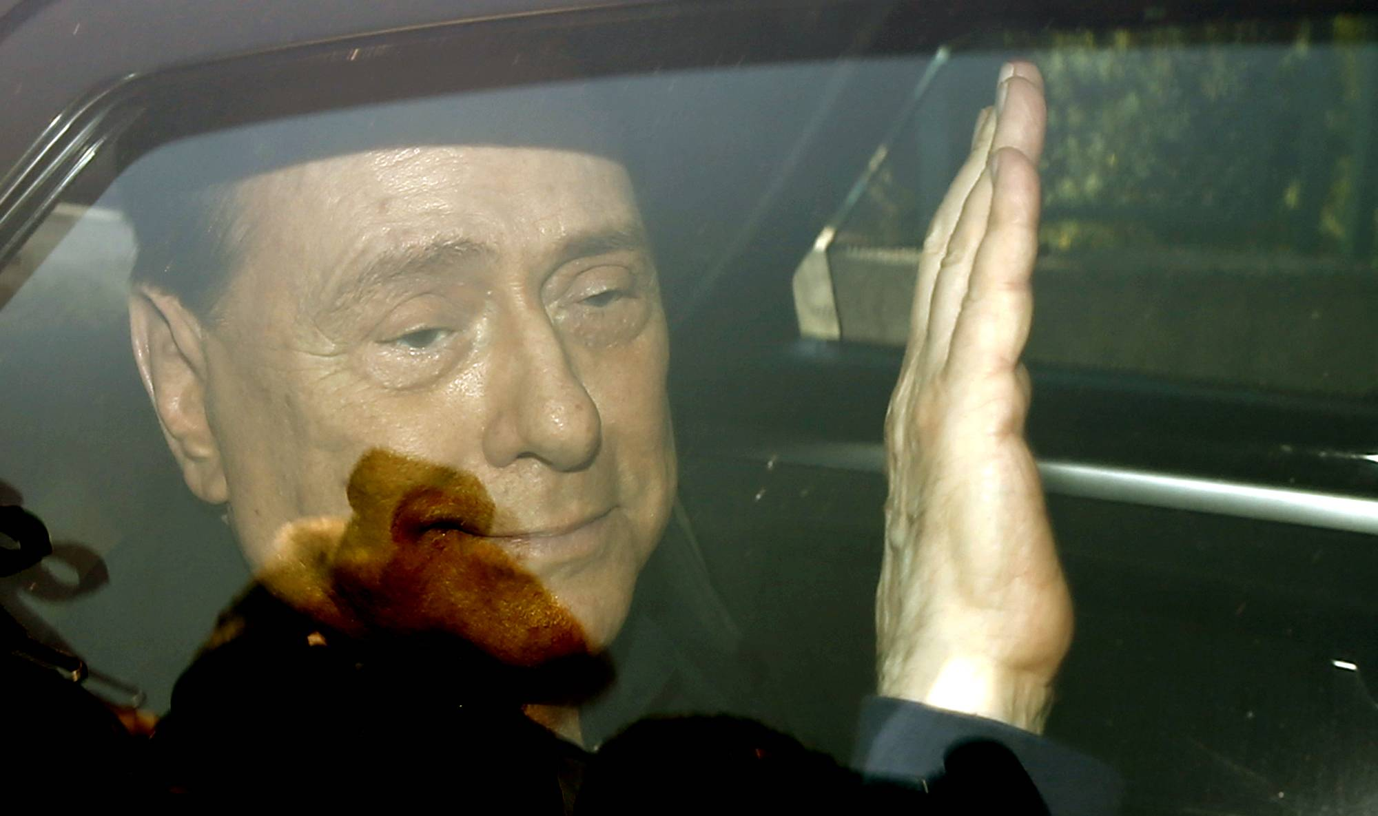 Italy's former Premier Silvio Berlusconi waves Friday as he leaves the 'Sacra Famiglia' institute in Cesano Boscone, Italy.  An Italian appeals court has acquitted the former premier in a sex-for-hire case.