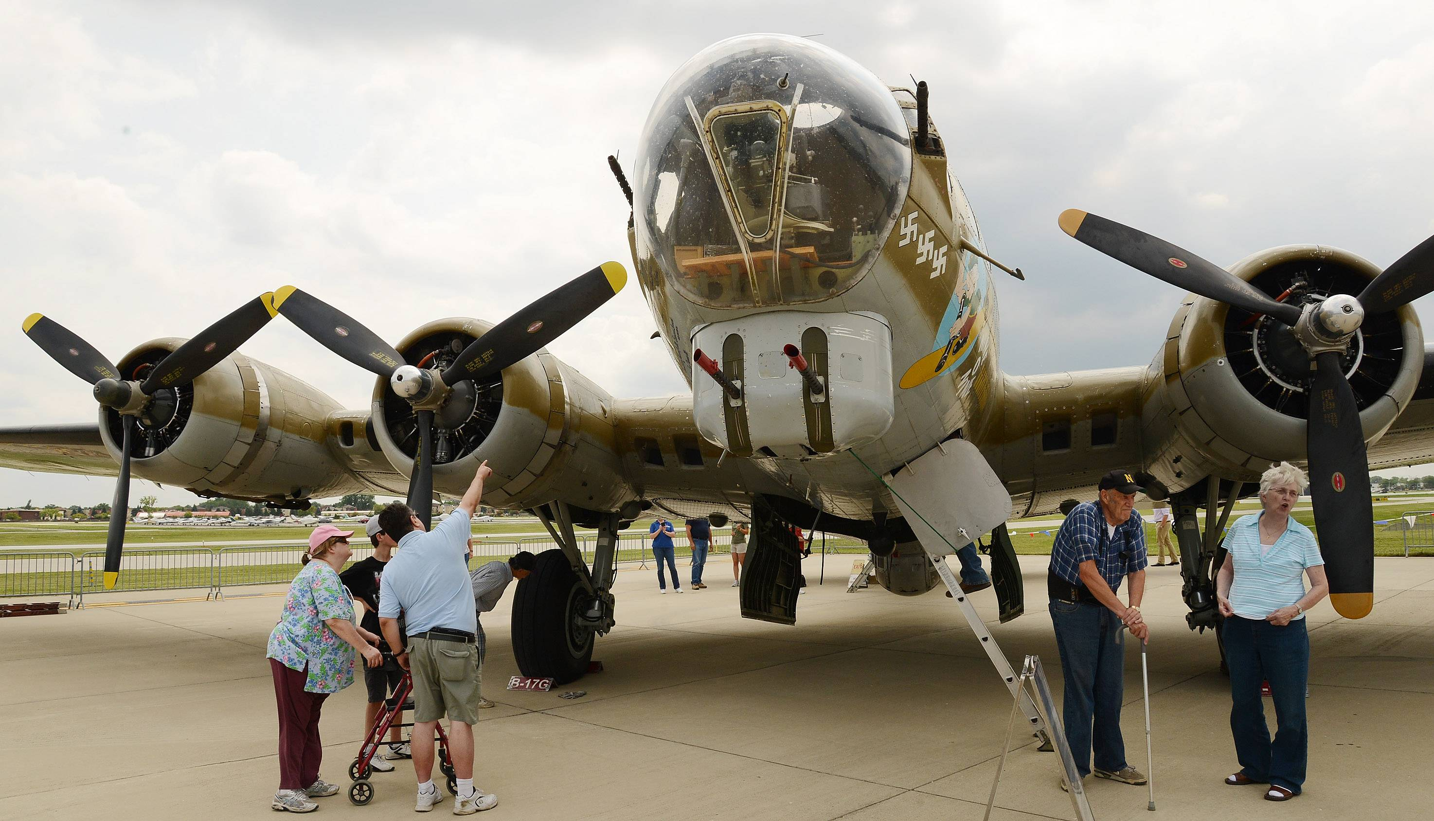 Mark Farina, of Brookfield, shows his wife Diane, left, and son Louis a B-17 Flying Fortress. Diane's father, Casey Paulinski, co-piloted the WWII-era bomber.