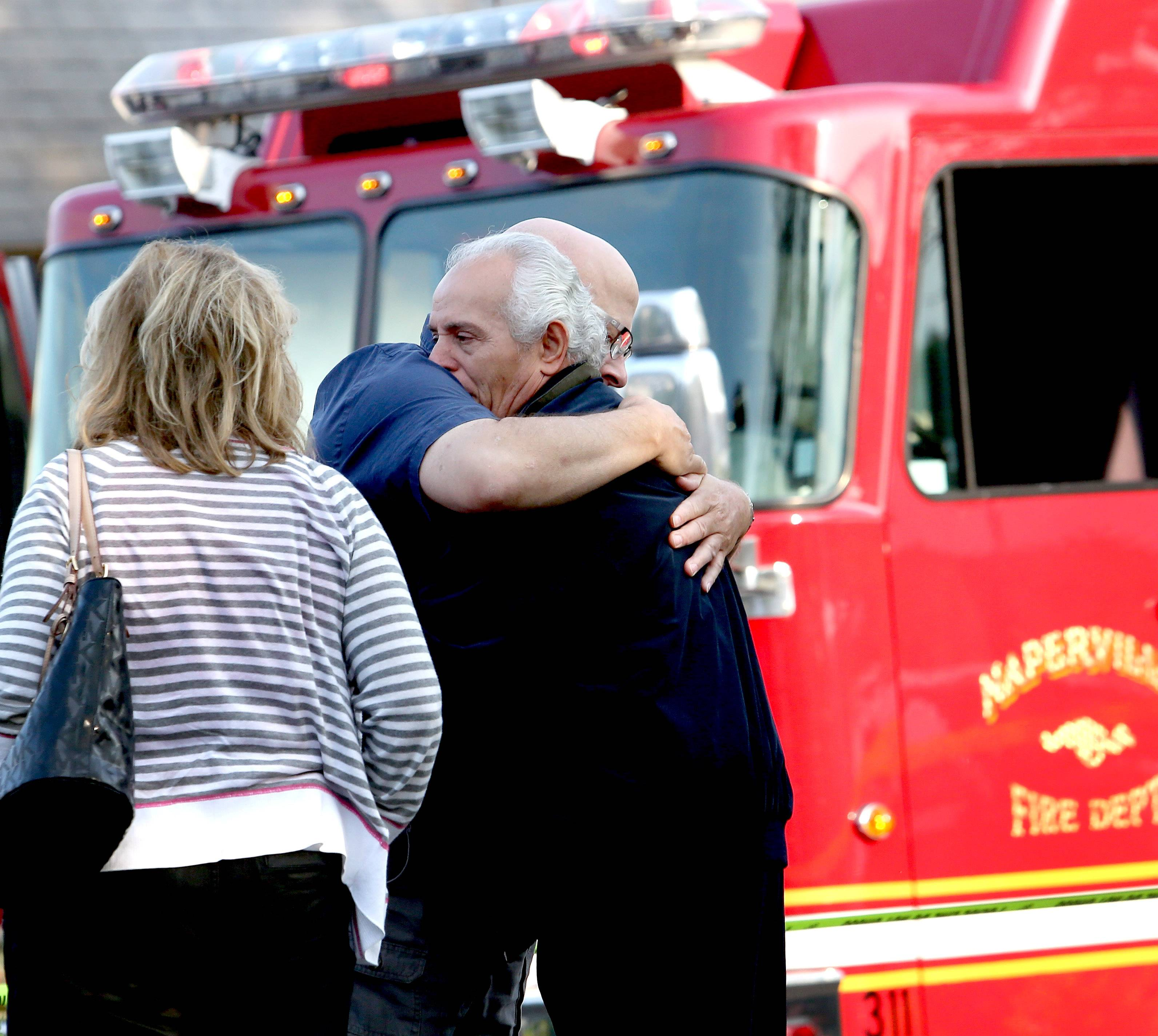 One of the owners of Grandma Sally's gets a hug after fire did extensive damage to the restaurant Friday morning in Naperville.