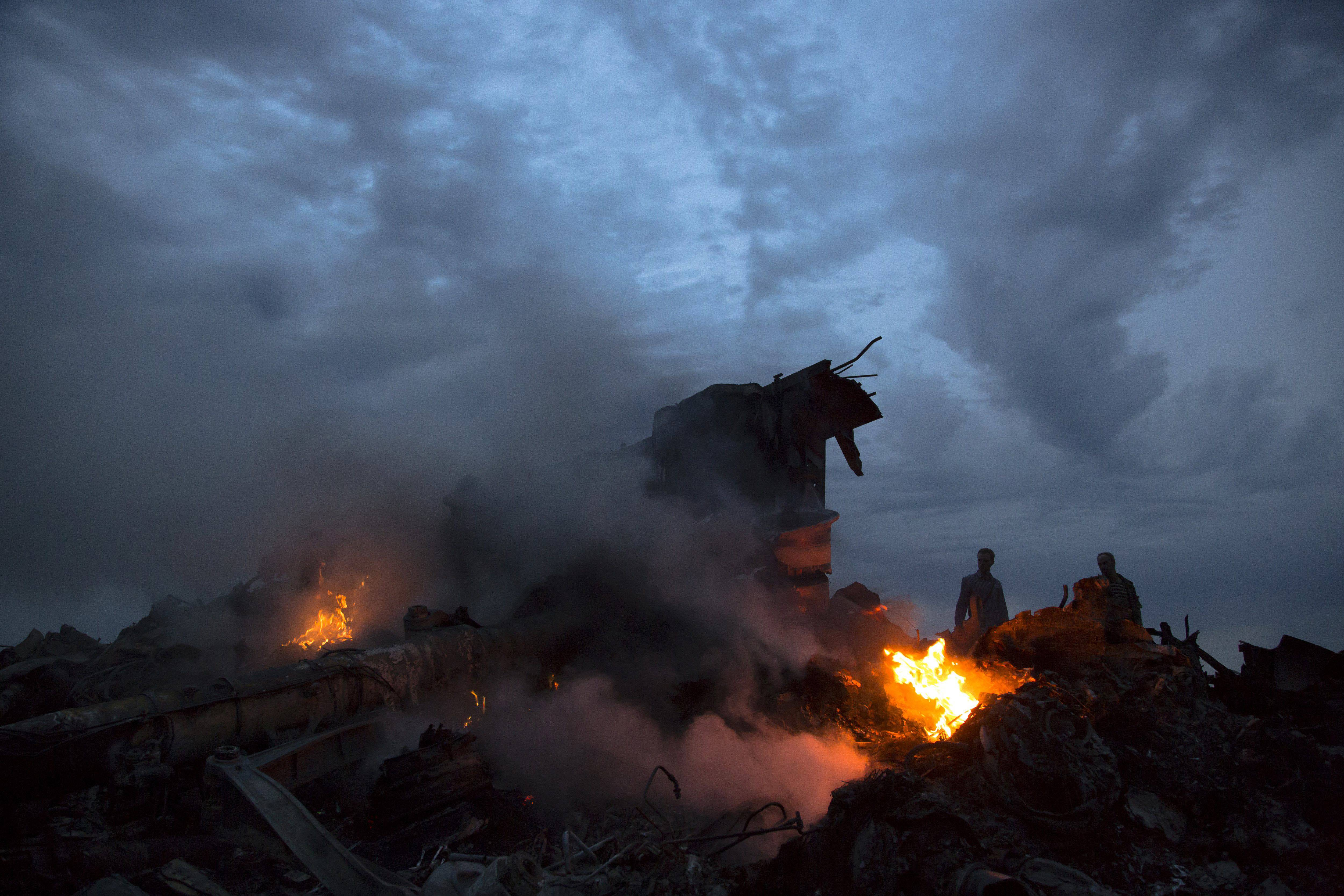 People walk amongst the debris Thursday at the crash site of a passenger plane near the village of Grabovo, Ukraine. Ukraine said a passenger plane carrying 298 people was shot down Thursday as it flew over the country, and both the government and the pro-Russia separatists fighting in the region denied any responsibility for downing the plane.