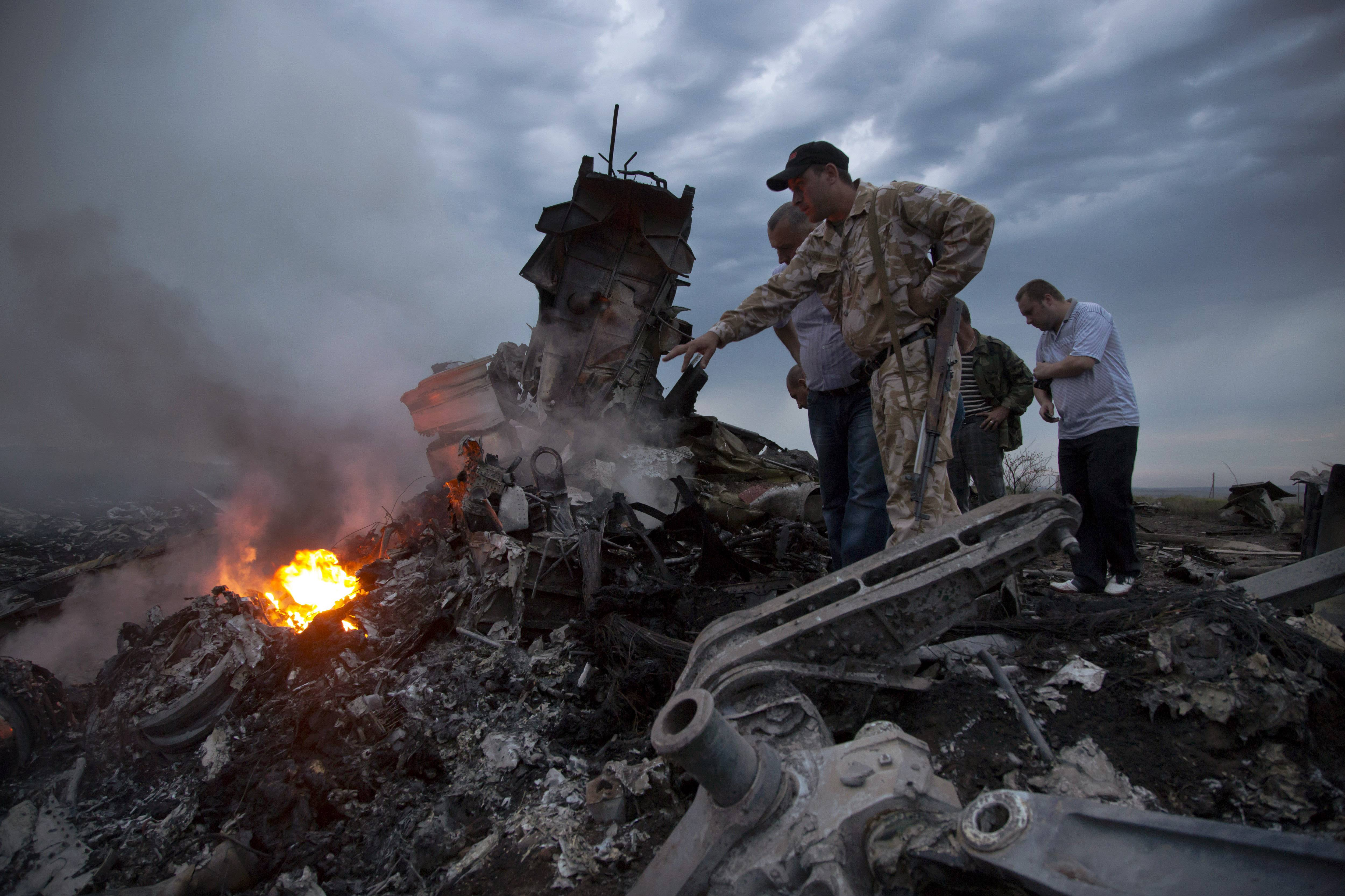 People inspect the crash site of a passenger plane near the village of Hrabove, Ukraine, yesterday. Ukraine said a passenger plane carrying 298 people was shot down as it flew over the country, and both the government and the pro-Russia separatists fighting in the region denied any responsibility for downing the plane.