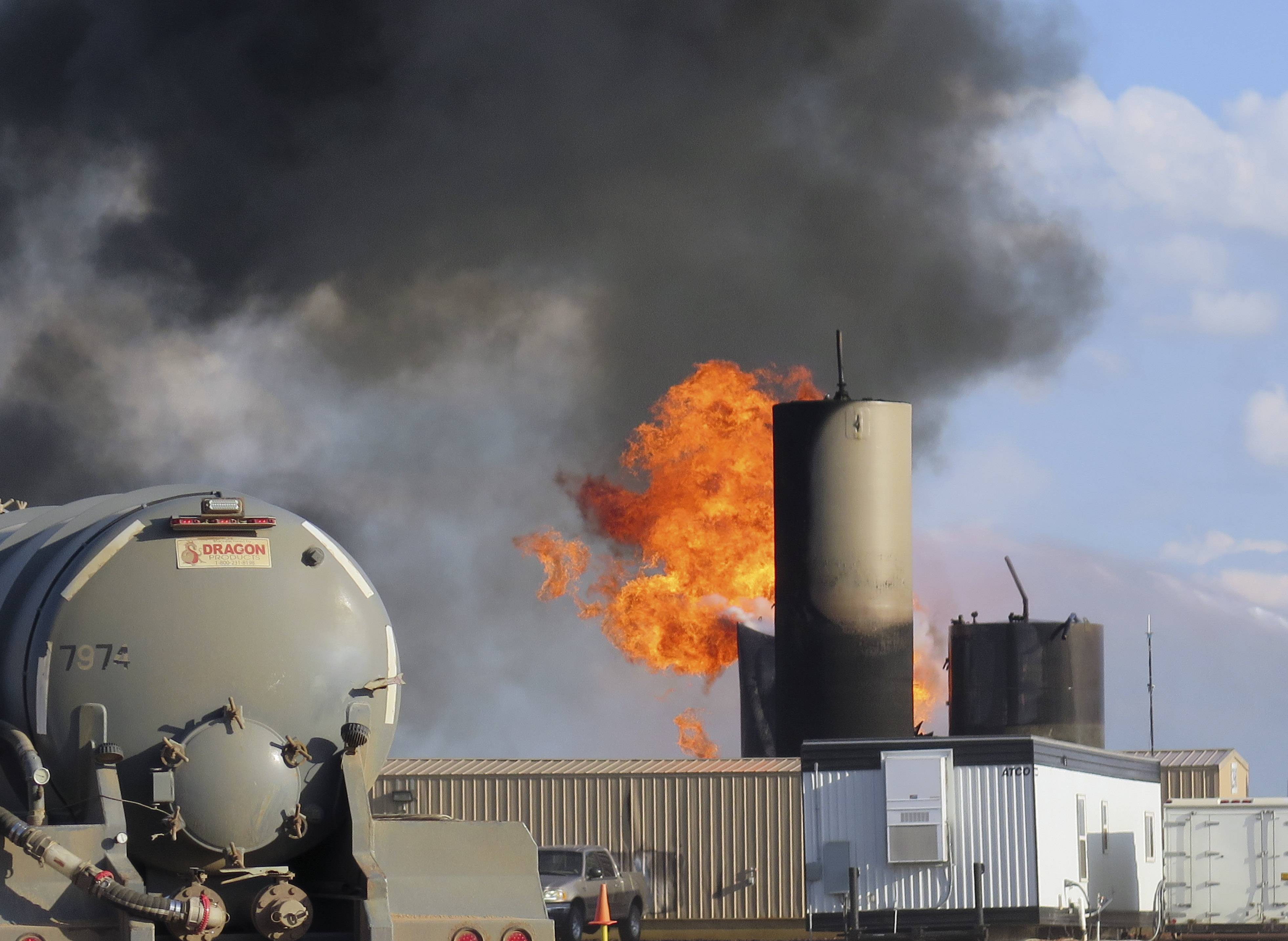 A saltwater disposal facility burns after it was struck by lightning, near Alexander, N.D.