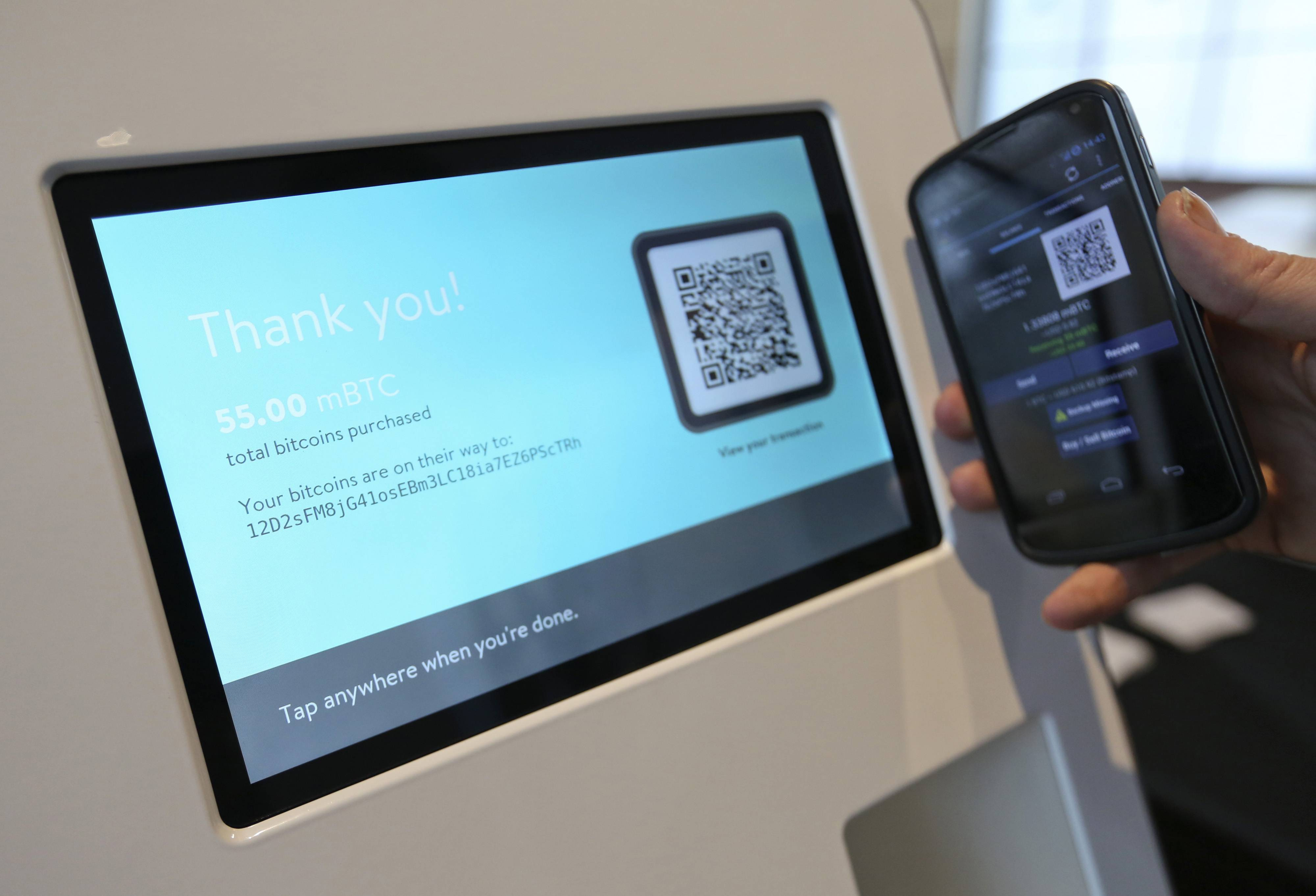 A customer confirms receipt of a bitcoin purchase with cash using a bitcoin automated teller machine (ATM) at the CoinSummit Virtual Currency conference in London, U.K.