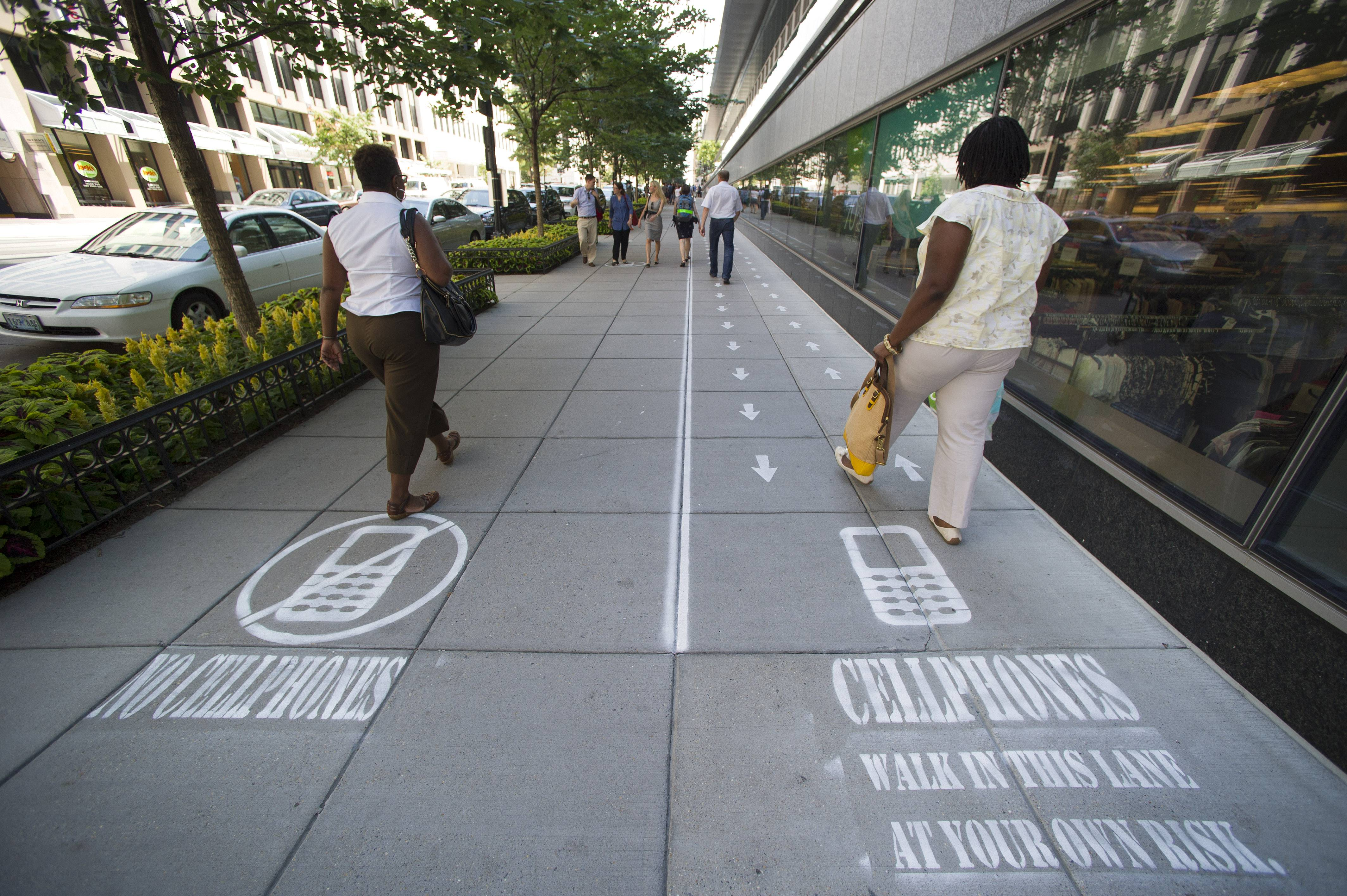 As part of their Mind Over Masses television show, National Geographic divided a one block-long sidewalk into two sections; one for cell phone users and the other for those not using a cell phone in downtown Washington, Thursday, July 17, 2014. The walkway warnings were put there by the brains behind a National Geographic television show as part of a behavioral science experiment.