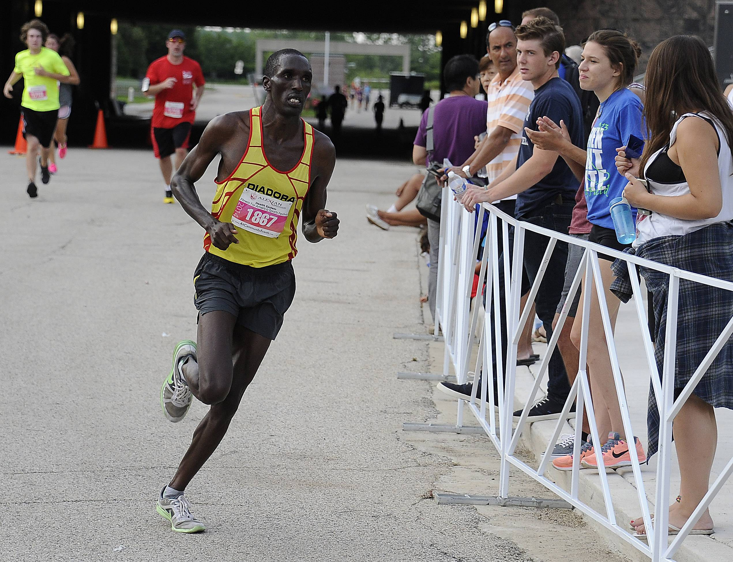 Patrick Cheptoek of Uganda wins the sixth annual Alexian Brothers Fitness for America Sports Festival half marathon race Saturday with a time of 1:4:50 as the crowd cheers him on near the finish in Hoffman Estates.