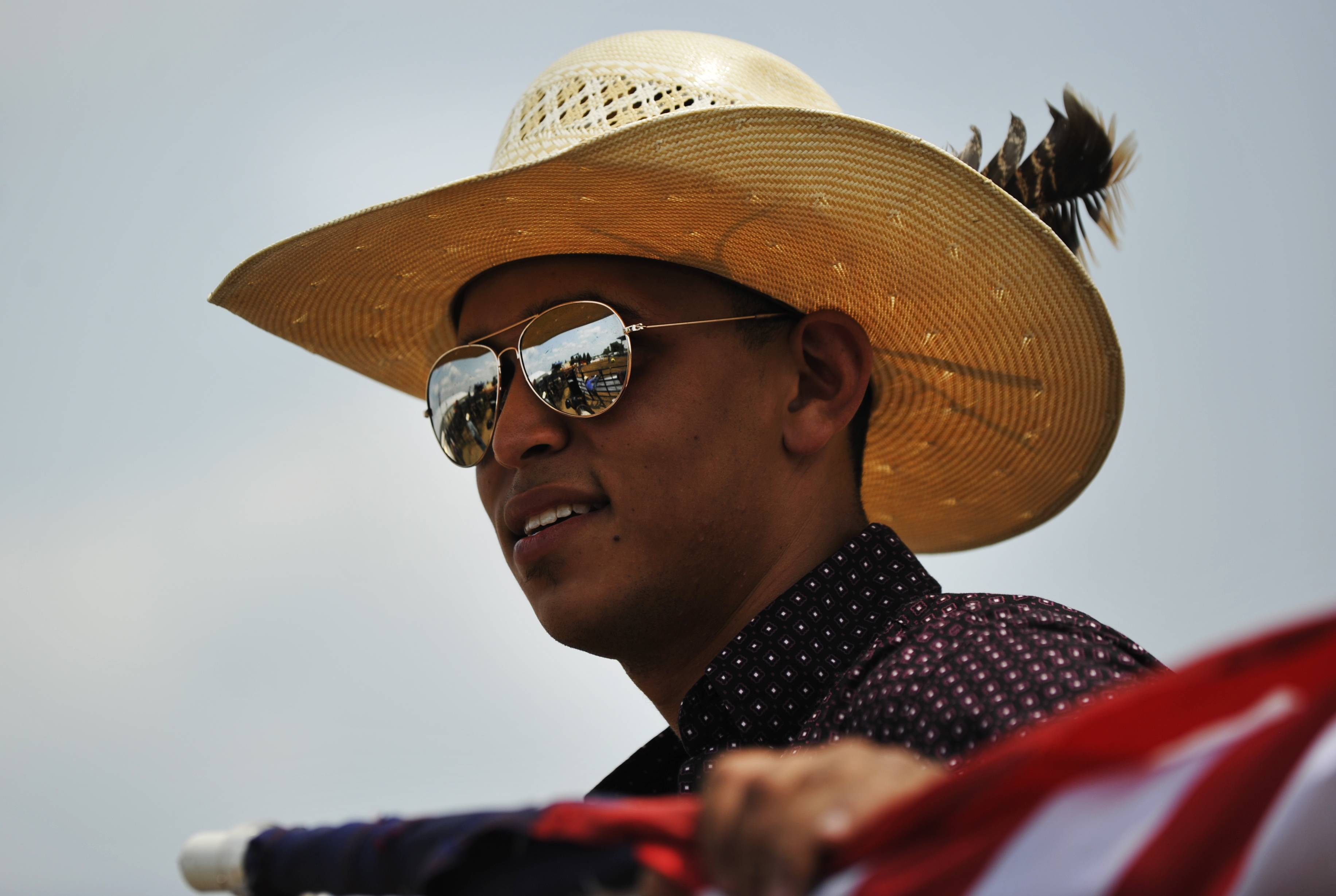 "Ricky Littlejohn of Parma, Michigan, holds the American flag as he glances into the ring before the second round of the Professional Bullriding Championship at the Kane County Fair. Littlejohn has been a ""pickup man,"" or bull wrangler, for more than 5 years and says he ""loves being on the road and rodeo life."""