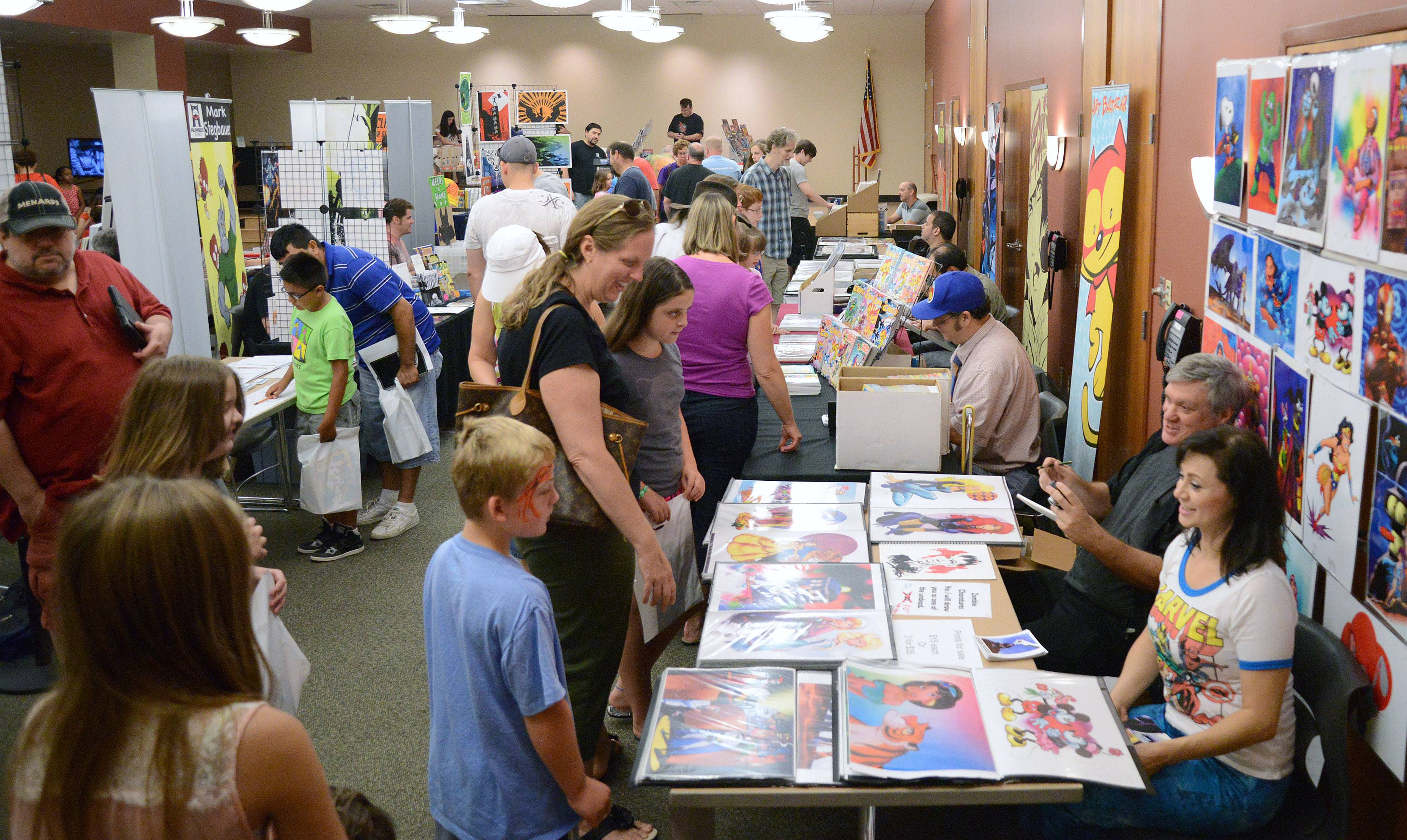 Katie Vaughn, center, of Elgin talks with artist Scott Beaderstadt and his assistant Angel Levine, both of Chicago, at the fifth annual Comic Book Mania Convention at the Gail Borden Library in Elgin on Saturday. Beaderstadt is well known for his imagery for Marvel, Disney and Trollords.