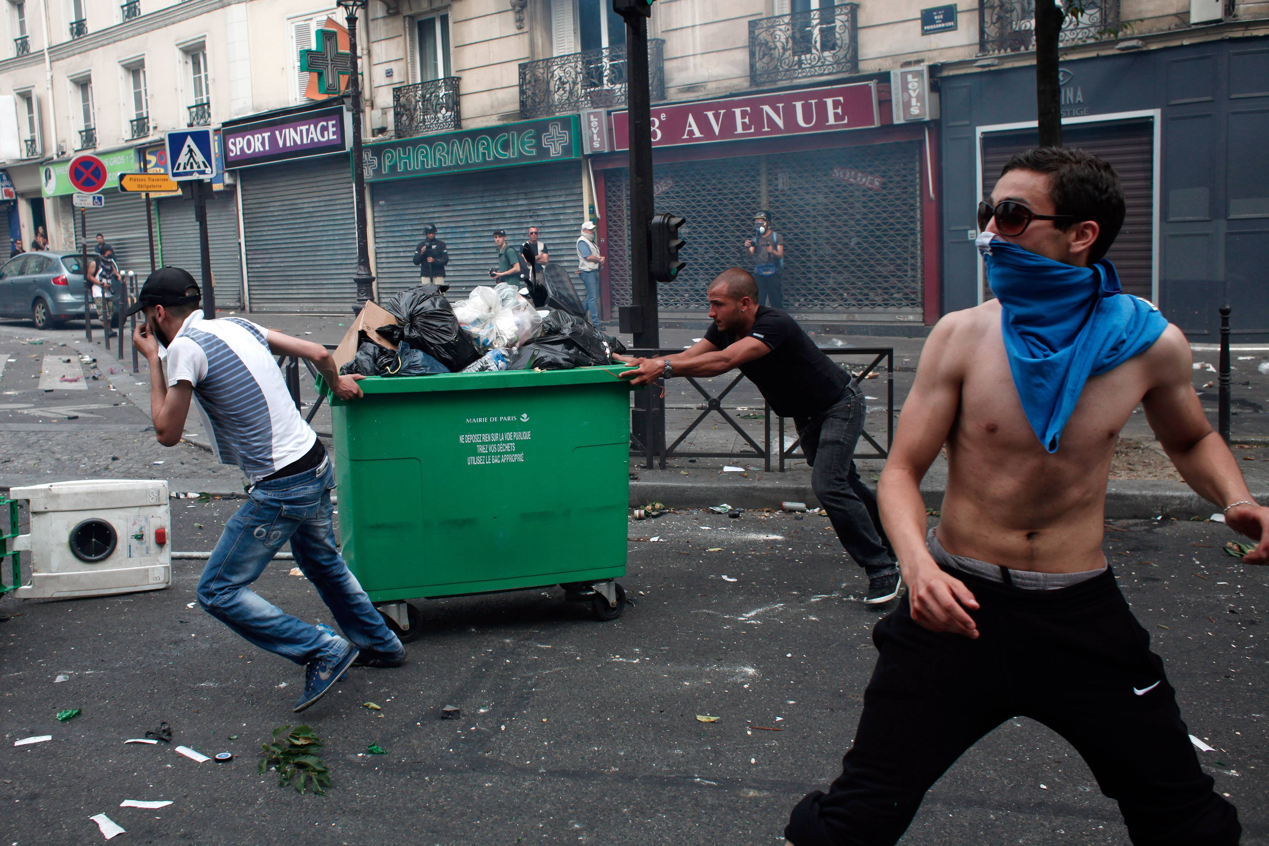 Pro-Palestinian demonstrators push a bin Saturday to raise a barricade, during a demonstration in Paris.