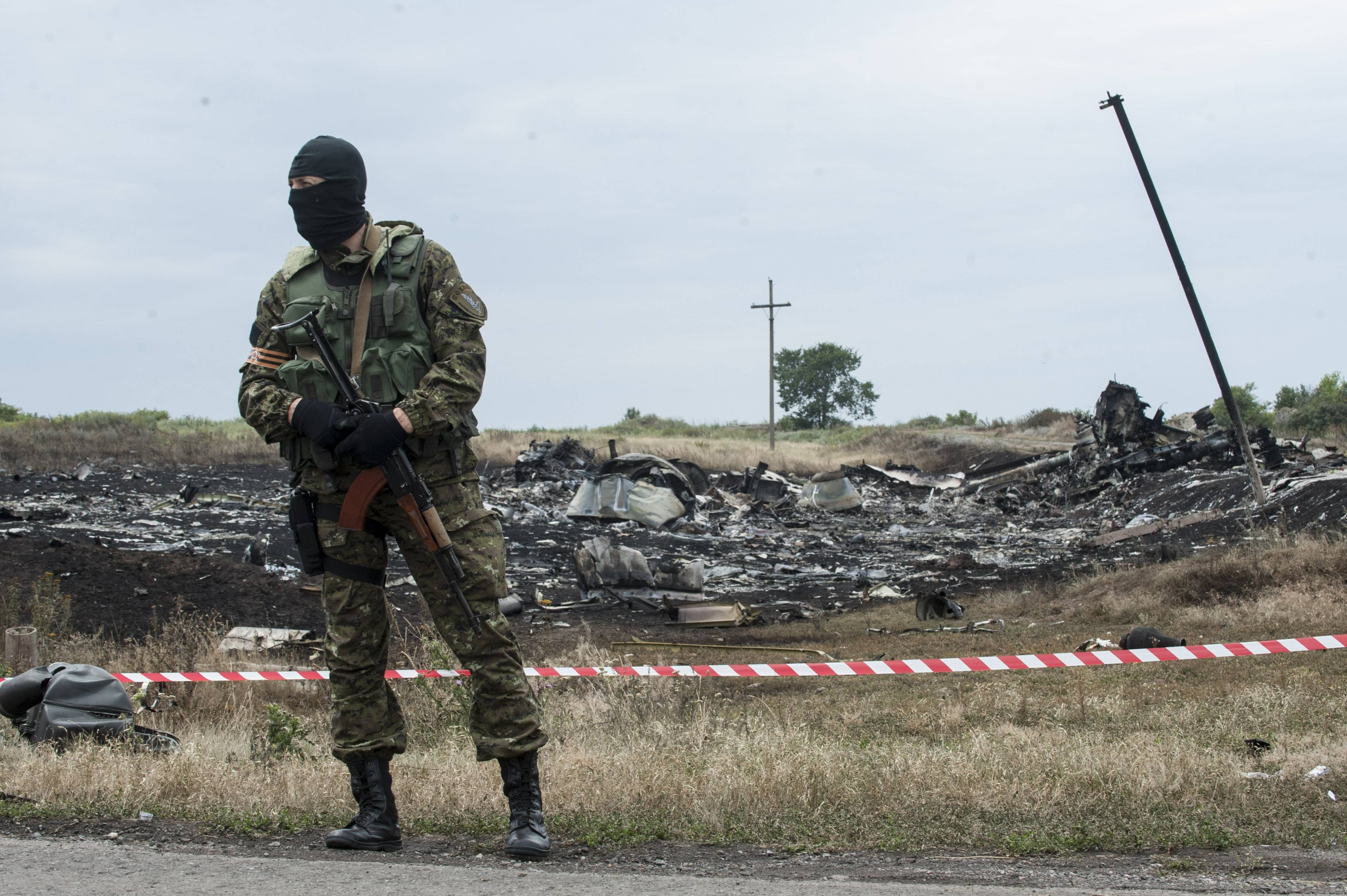 A pro-Russian fighter guards the crash site of a Malaysia Airlines jet near the village of Hrabove, eastern Ukraine, Saturday, July 19, 2014. Ukraine accused Russia on Saturday of helping separatist rebels destroy evidence at the crash site of a Malaysia Airlines plane shot down in rebel-held territory — a charge the rebels denied.