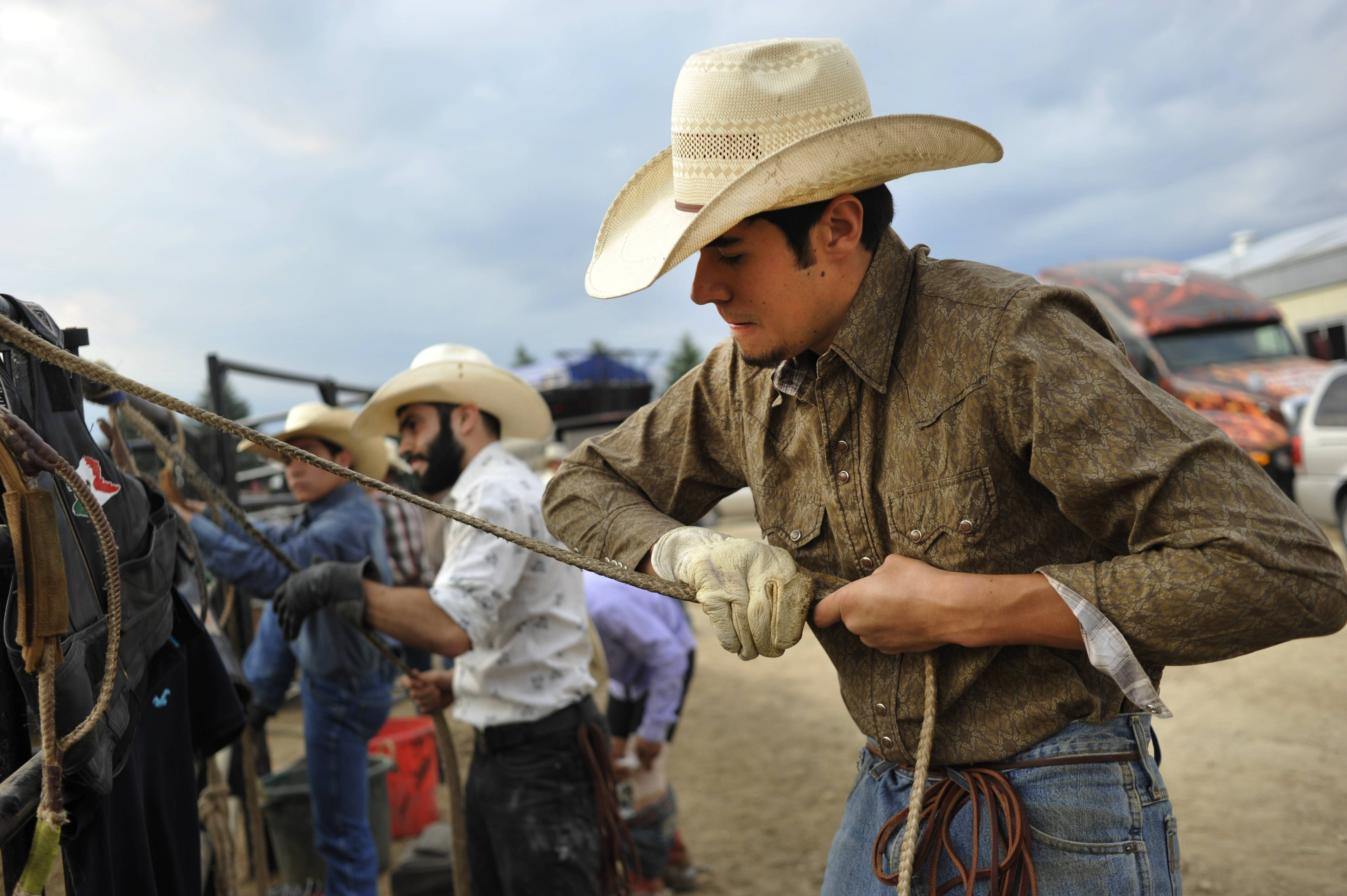"Brooke Herbert Hayes/bhayes@dailyherald.com Enrique Lopez of Oswego and Brian Garcia of Joliet, rosin, or prepare, their ropes with other riders before the Professional Championship Bullriding at the Kane County Fair at the Fairgrounds in St. Charles on Friday. Lopez became on hooked on bullriding from his first try, ""you get on the first time and then you love it."""