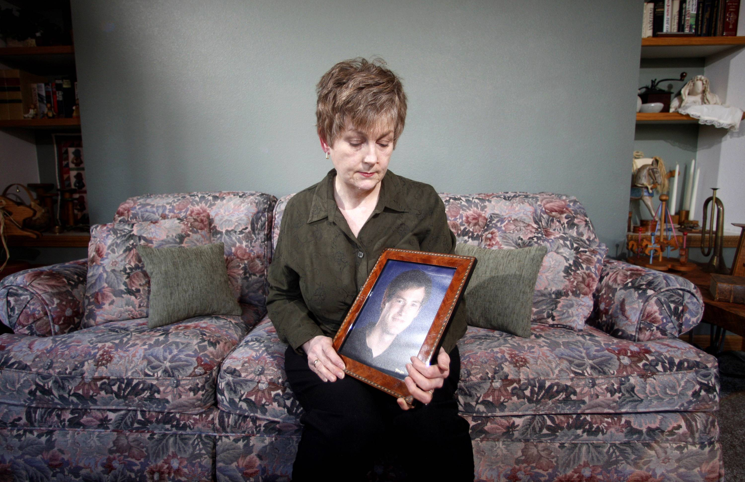 In this Monday, Feb. 27, 2012 file photo, Karen Williams, who sued Facebook for access to her 22-year-old son Loren's account after he died in a 2005 motorcycle accident, looks at a portrait of her son at her home in Beaverton, Ore. The Uniform Law Commission on Wednesday, July 16, 2014 was expected to endorse a plan to automatically give loved ones access to -- but not control of -- all digital accounts, unless otherwise specified.