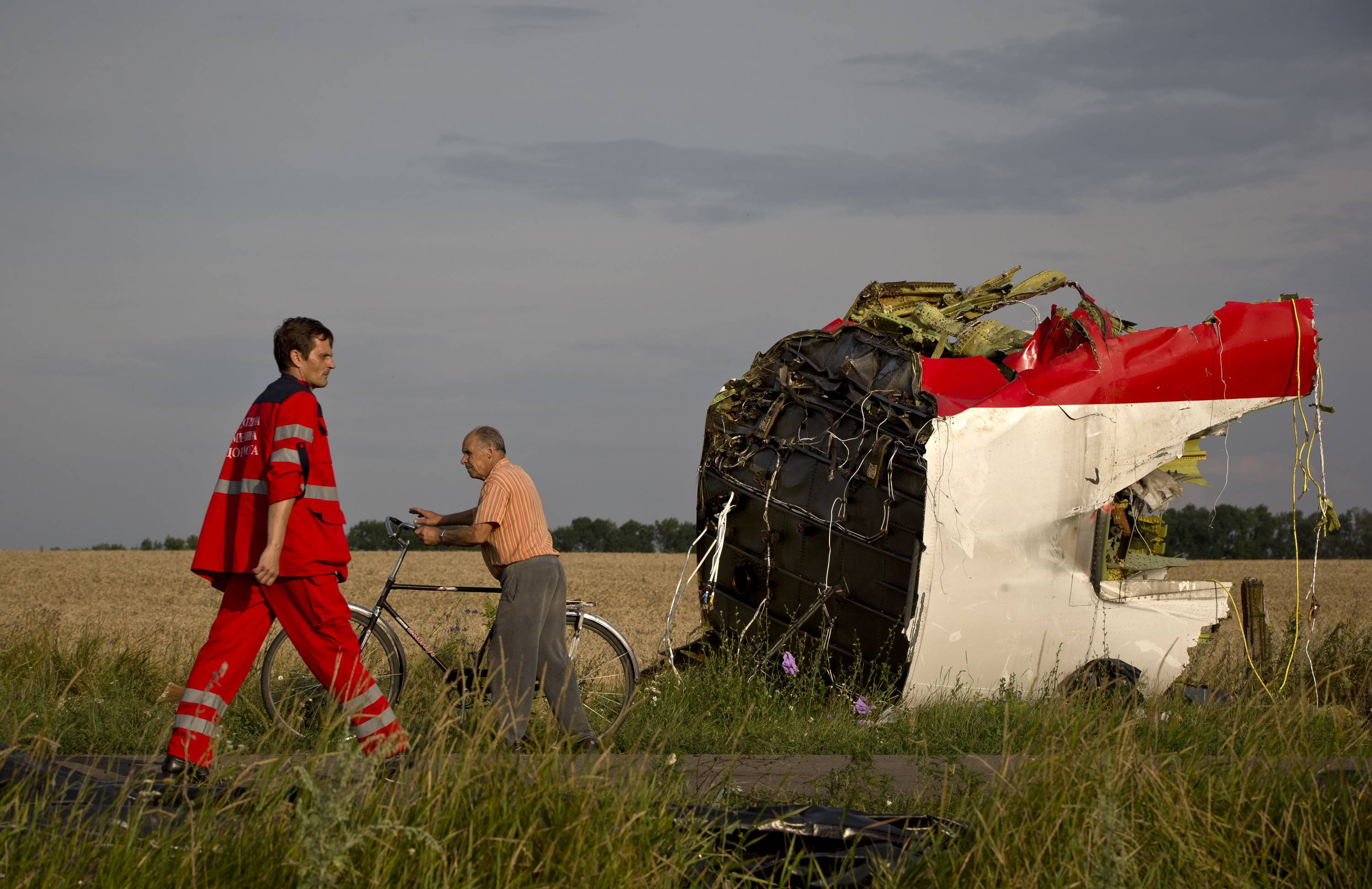 A paramedic walks by a part of fuselage Saturday at the crash site of Malaysia Airlines Flight 17 near the village of Hrabove, eastern Ukraine.