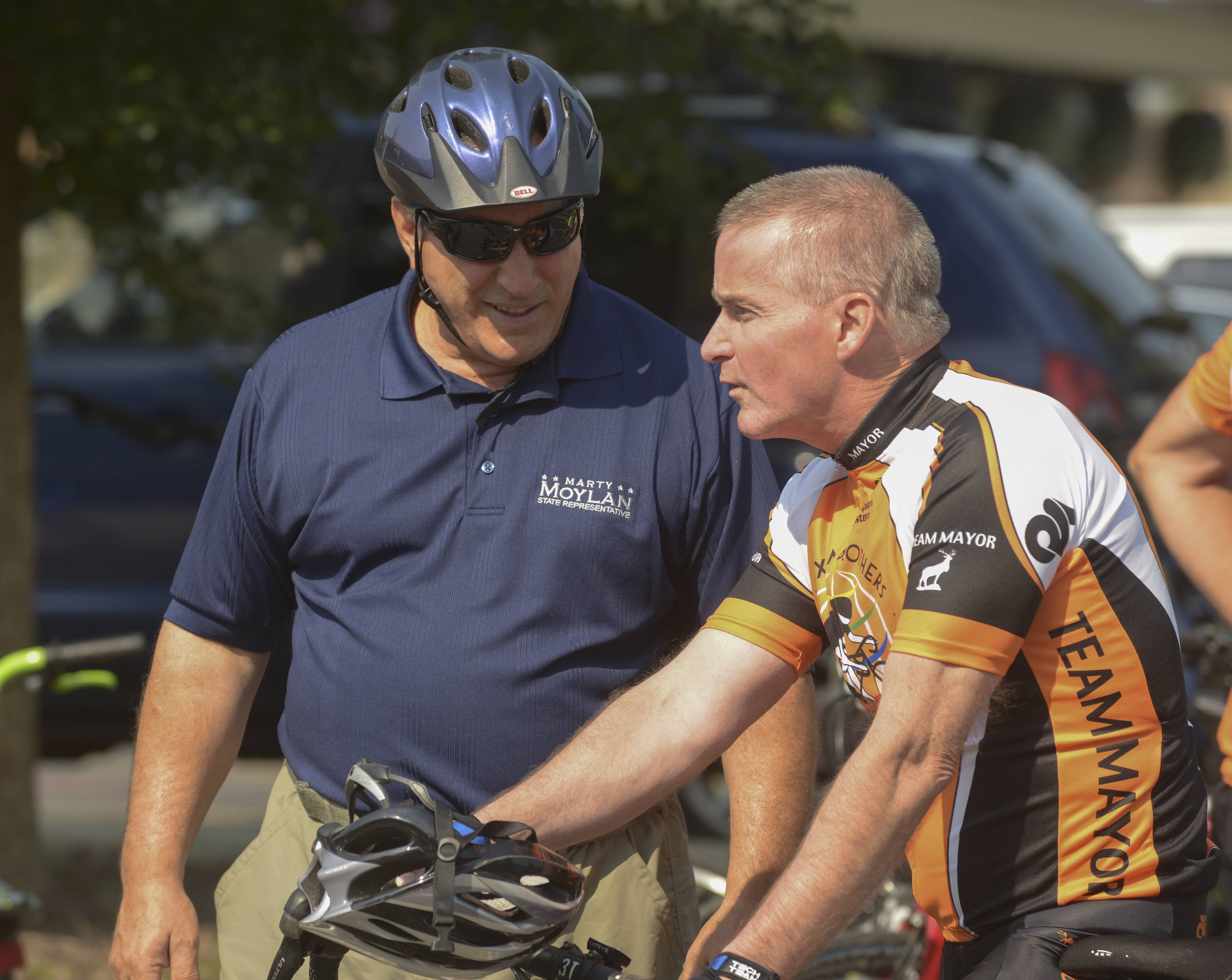 State Rep. Marty Moylan and Elk Grove Village Mayor Craig Johnson talk before leading cyclists around Elk Grove Village Saturday to encourage cycling.
