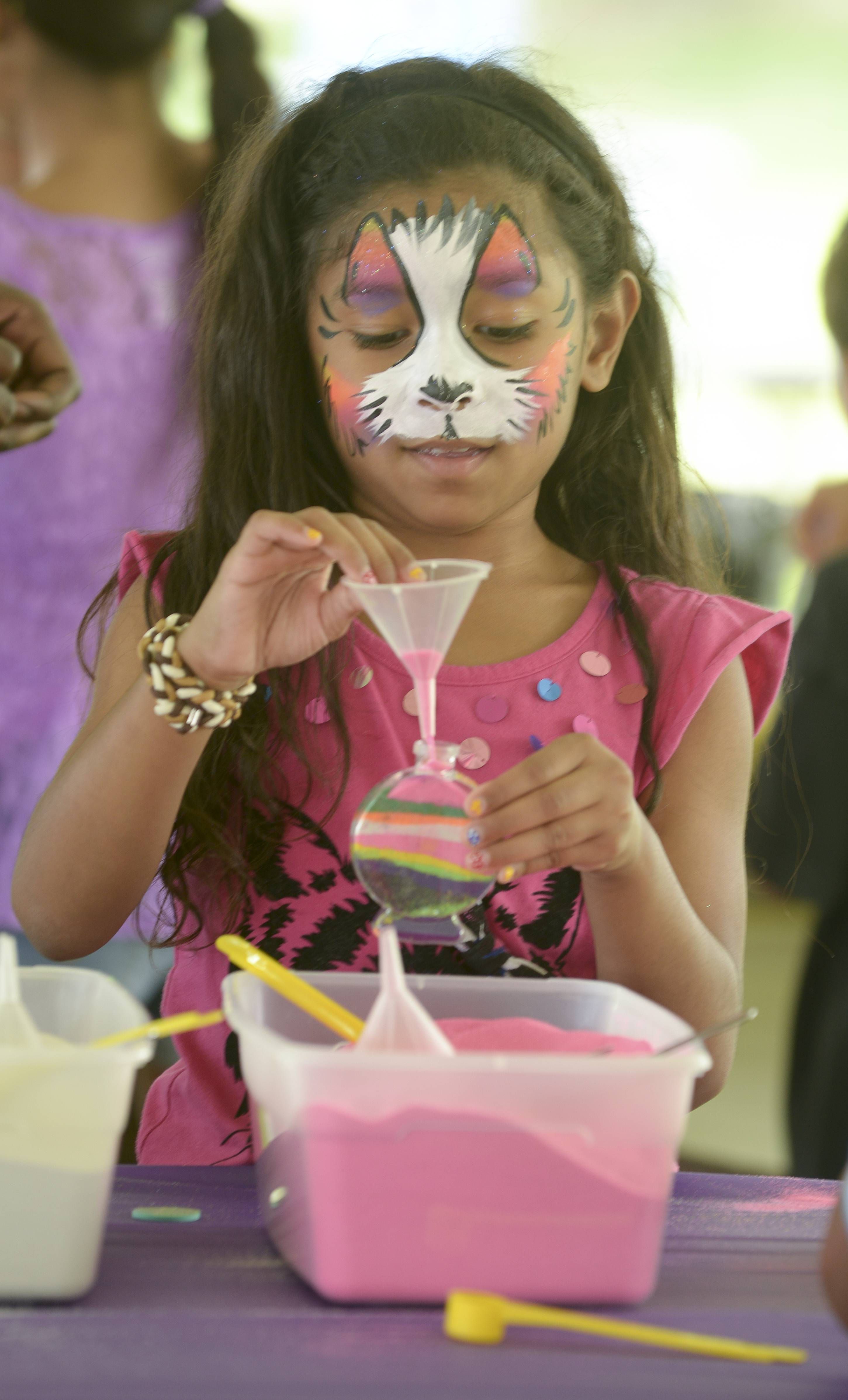 Her face painted, Jadalynn Chatman, 8, of Gurnee makes sand art Saturday while attending the Vernon Hills Summer Celebration.