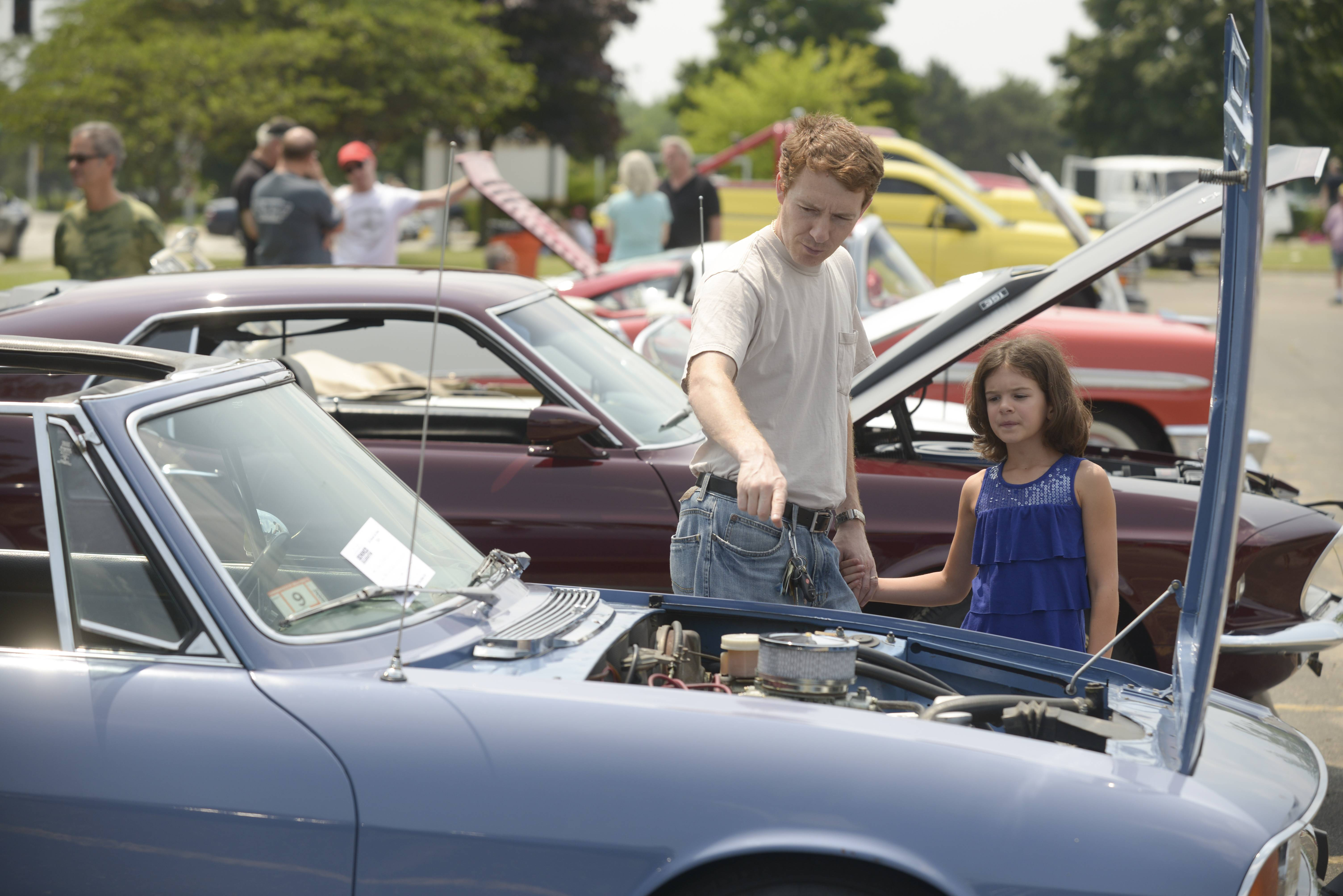 Igor Burda and his daughter Victoria, 8, of Vernon Hills check out the engine of the a 1973 Triumph Stag at the car show Saturday during the Vernon Hills Summer Celebration.