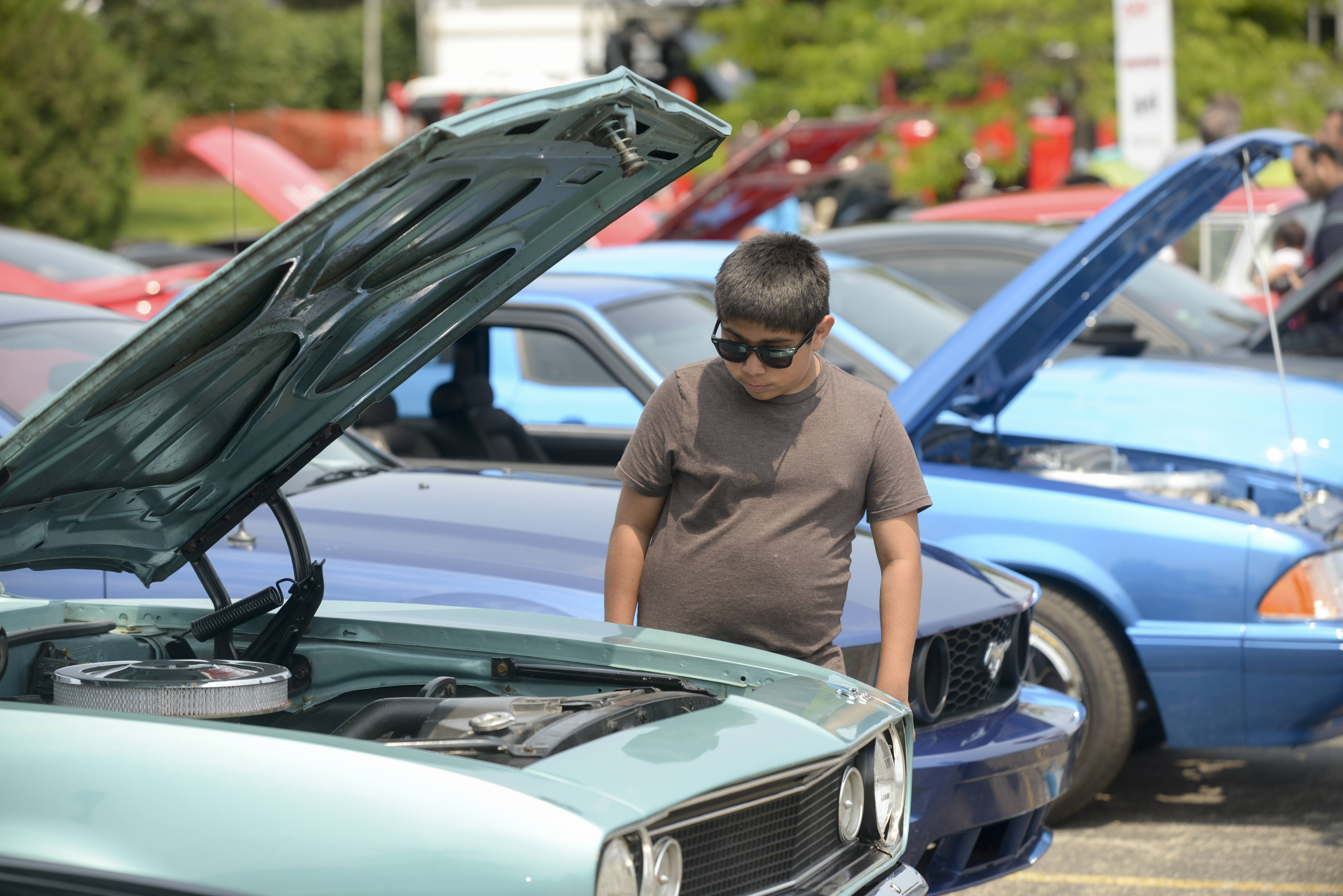 Steven Paredes, 11, of Mundelein checks out the engine of the a 1967 Camaro at the car show Saturday during the Vernon Hills Summer Celebration.