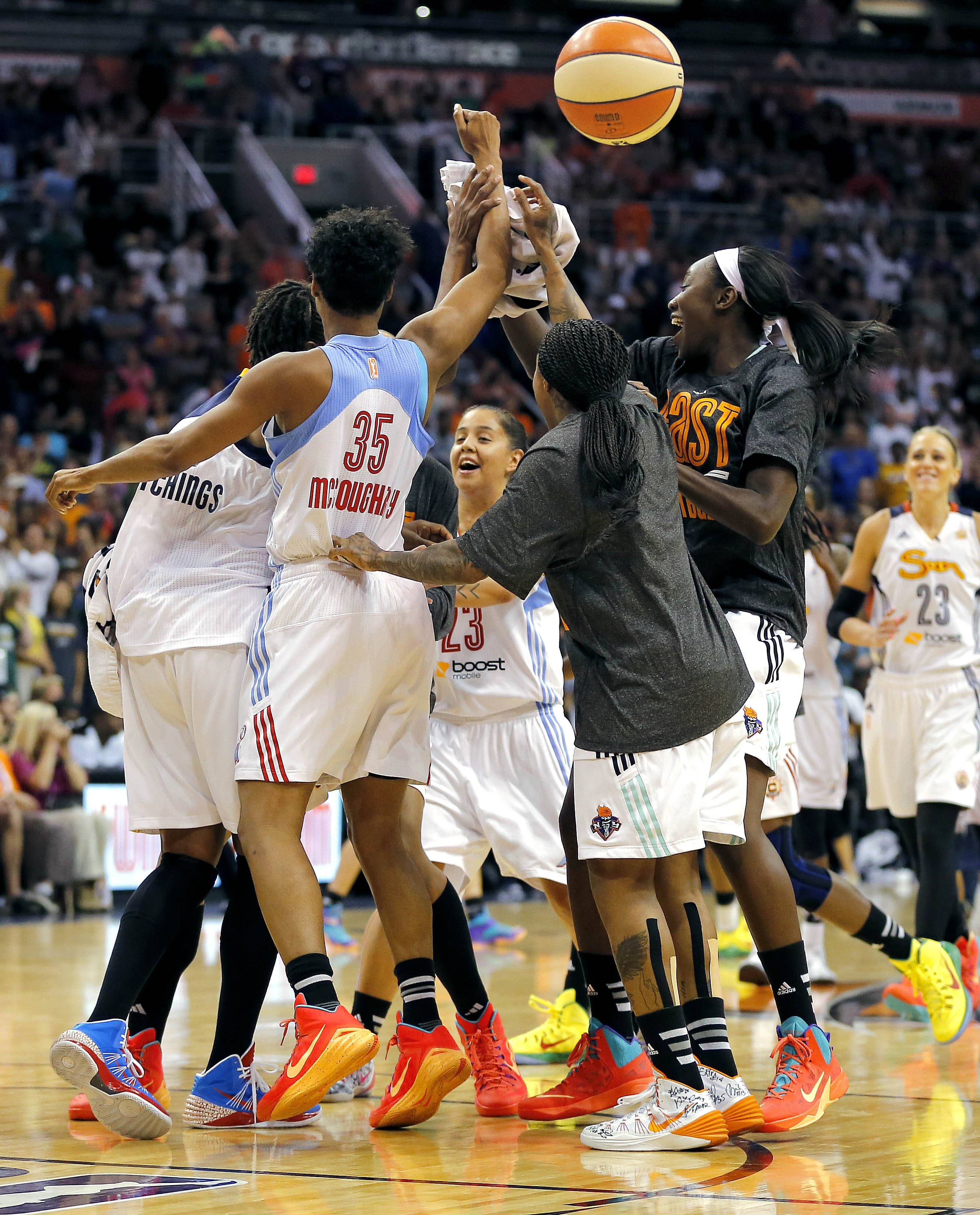 East players celebrate as time expires in overtime of the WNBA All-Star basketball game Saturday in Phoenix. The East won 125-124 in overtime.