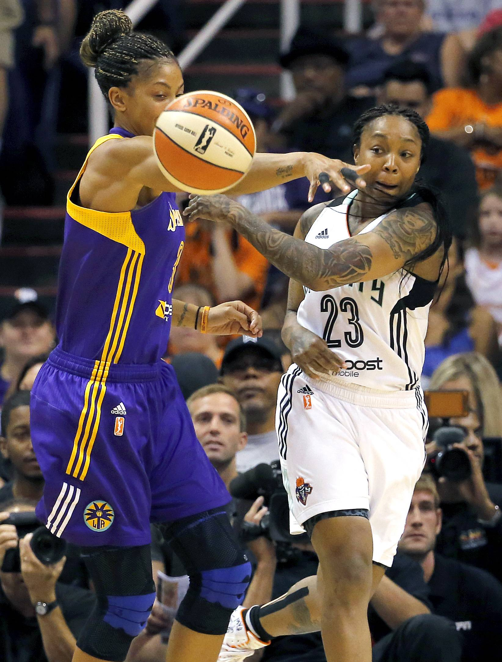 East's Cappie Pondexter, of the New York Liberty, dishes off under pressure from West's Candace Parker, a Naperville native who plays for the Los Angeles Sparks, during the WNBA All-Star basketball game Saturday in Phoenix.