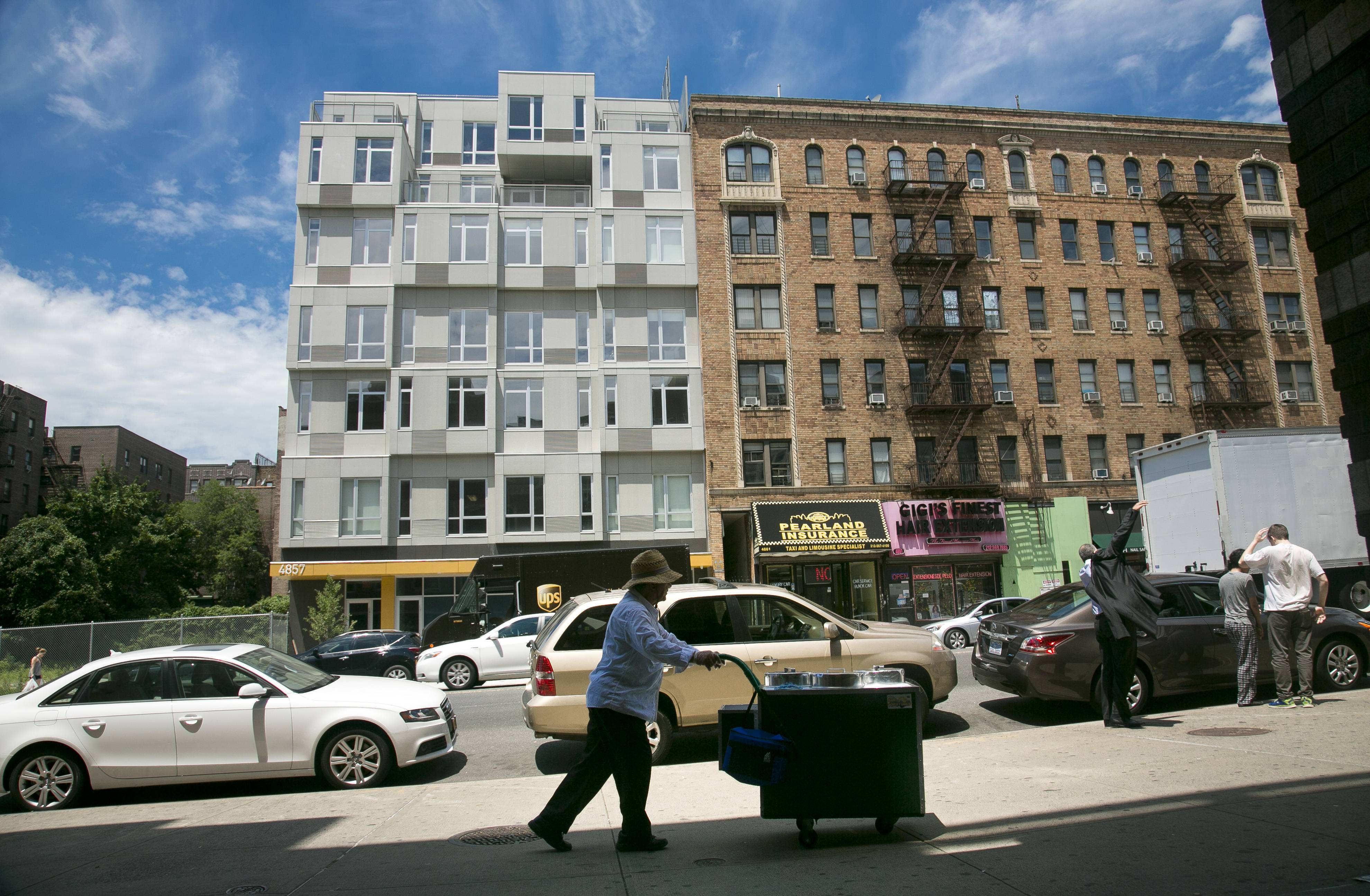 A seven-story modern modular apartment building called the Stack, left, is shown next to a decades-old residence in New York City. The Stack's 28 apartments were formed from 59 modules of rectangular components all 12.5 feet wide and 50 to 60 feet long. It's billed as the first multistory, modular-built apartment building to open in the city.
