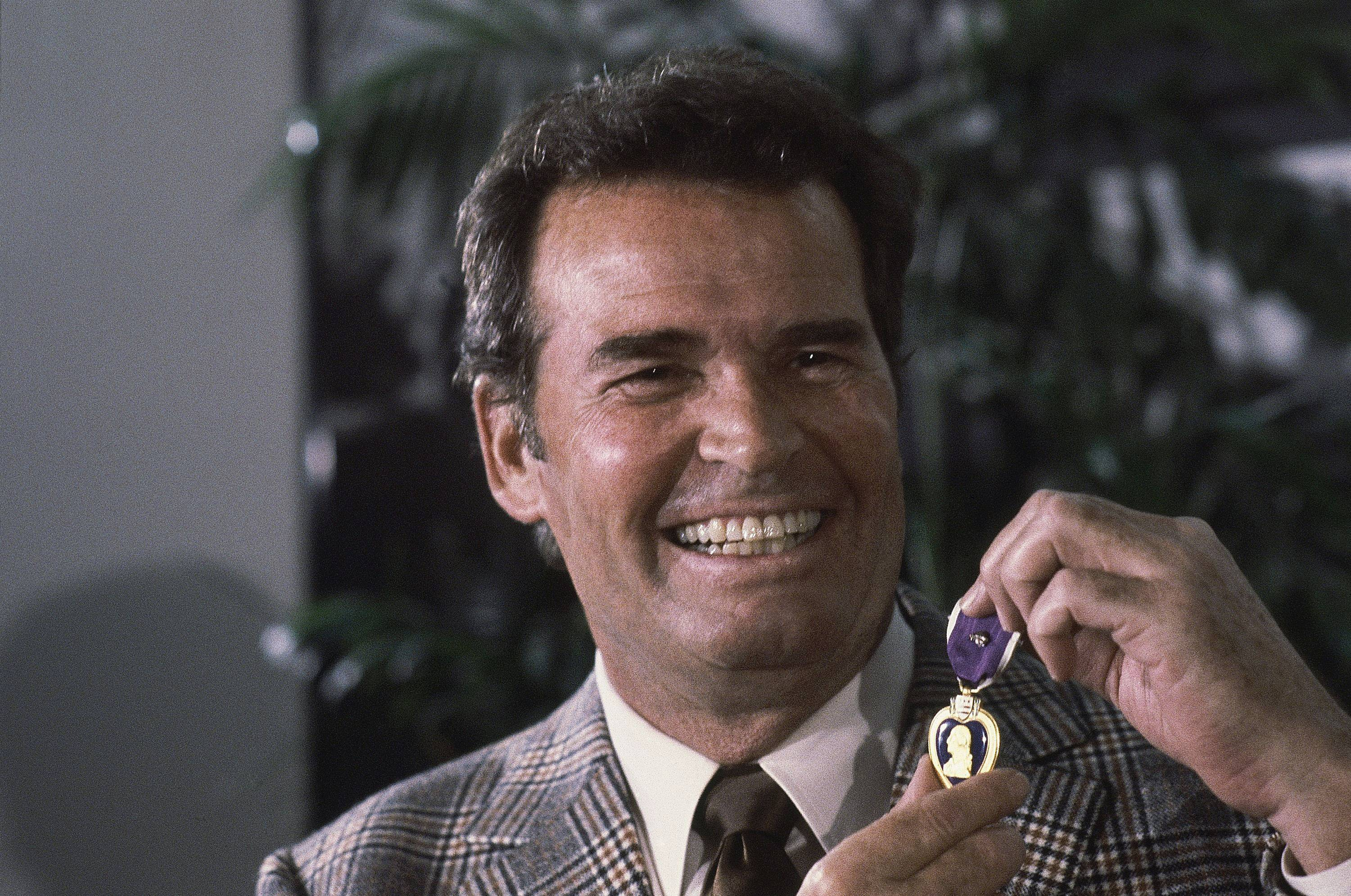 "Actor James Garner, left, smiles as he holds up the Purple Heart medal presented to him in a ceremony in this Monday, Jan. 24, 1983 file photo taken Los Angeles, Calif. Garner was wounded in April 1951 while with U.S. Forces in Korea, but his medal was never presented to him. Actor James Garner, wisecracking star of TV's ""Maverick"" who went on to a long career on both small and big screen, died Saturday July 19, 2014 according to Los angeles police. He was 86."