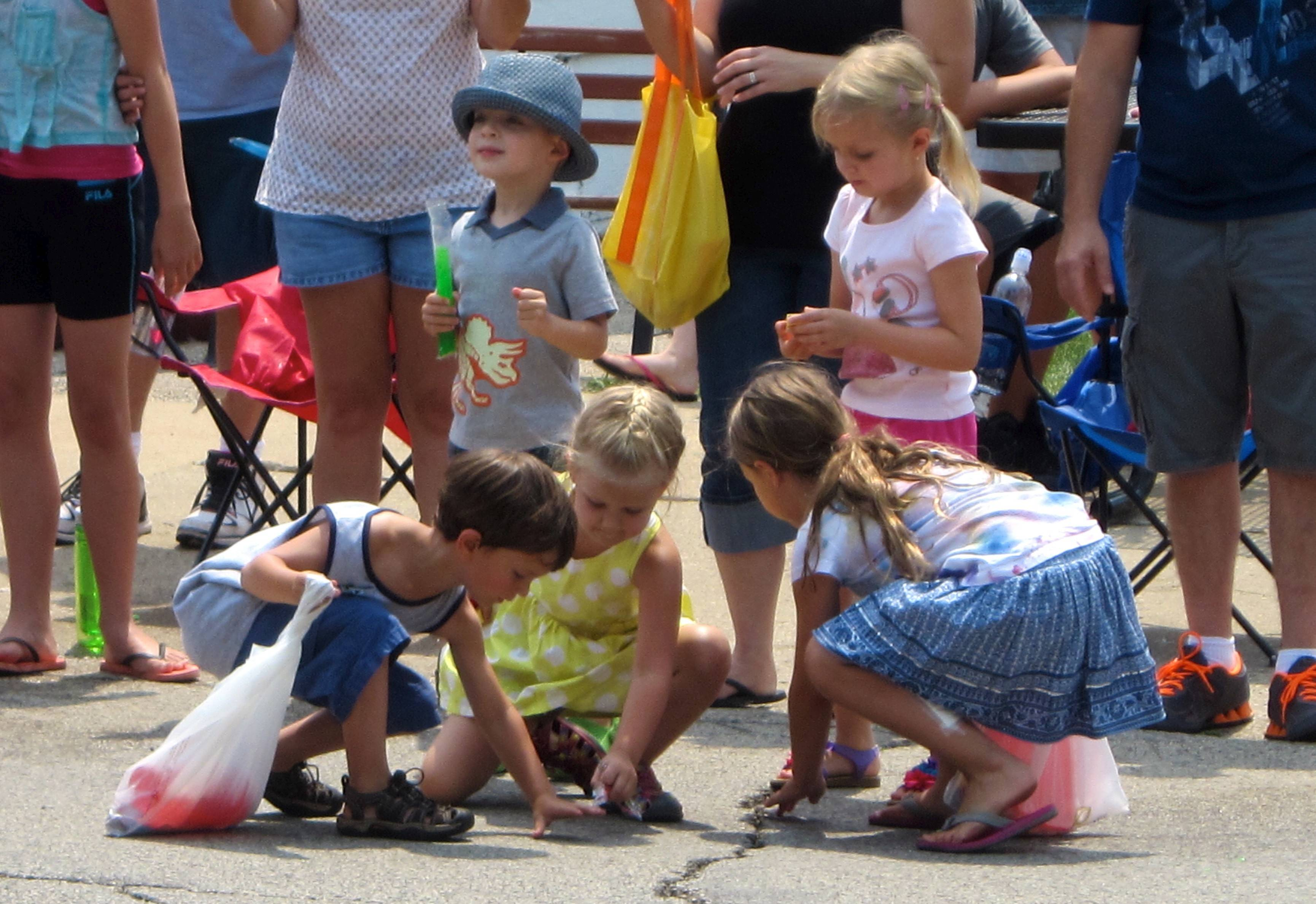 Children scramble to pick up candy thrown by marchers in the annual Alpine Fest Parade on Sunday in downtown Lake Zurich. The parade kicked off the last day of the annual summer event Alpine Fest.