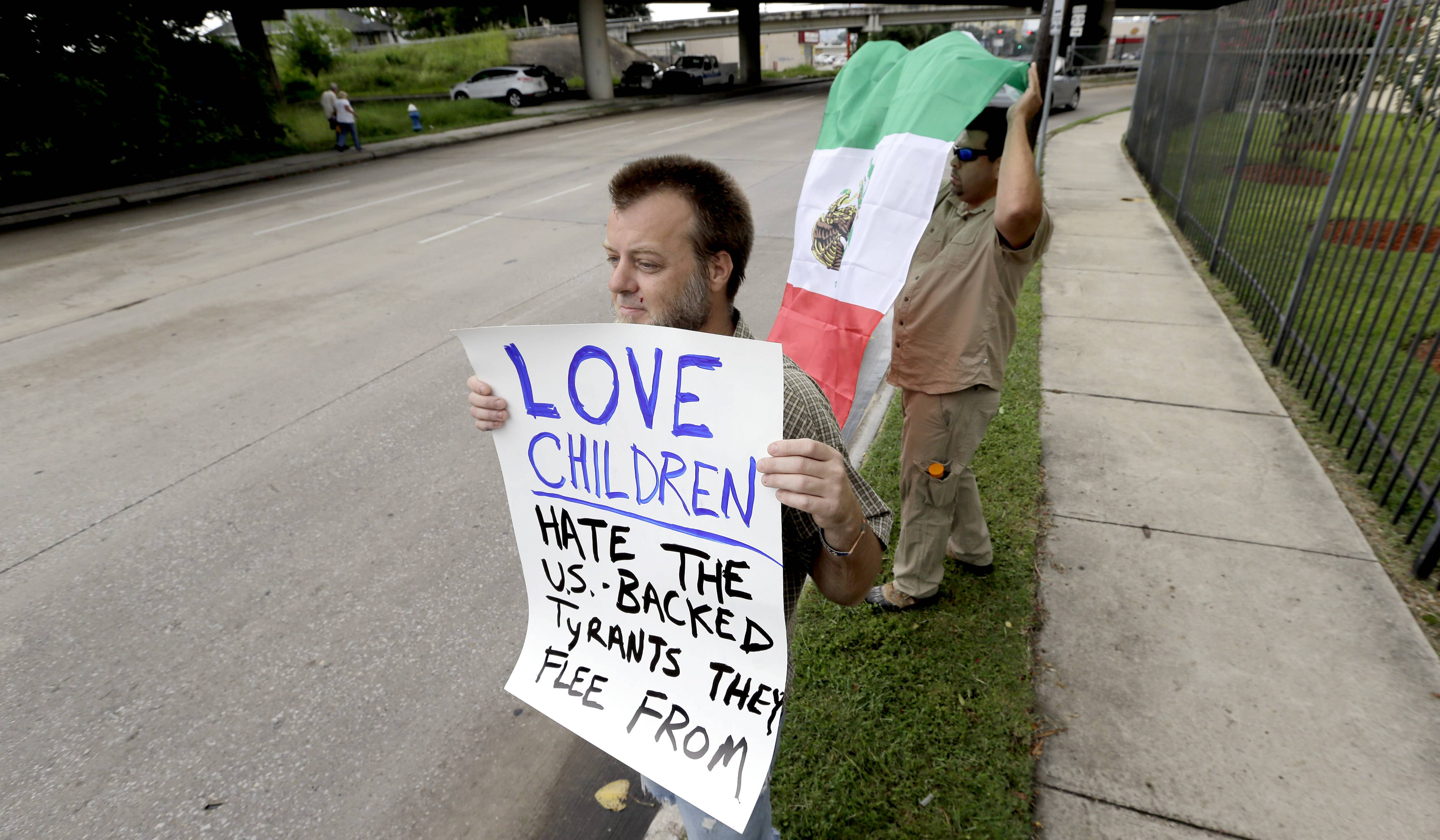 Bill Lambert holds a sign as he joins demonstrators outside the Mexican Consulate on Friday in Houston. The sharp contrast in how Americans are reacting to the immigrant influx mirrors the divisiveness seen in Congress as the nation's leaders attempt to find solutions to an issue that could worsen in the coming months.