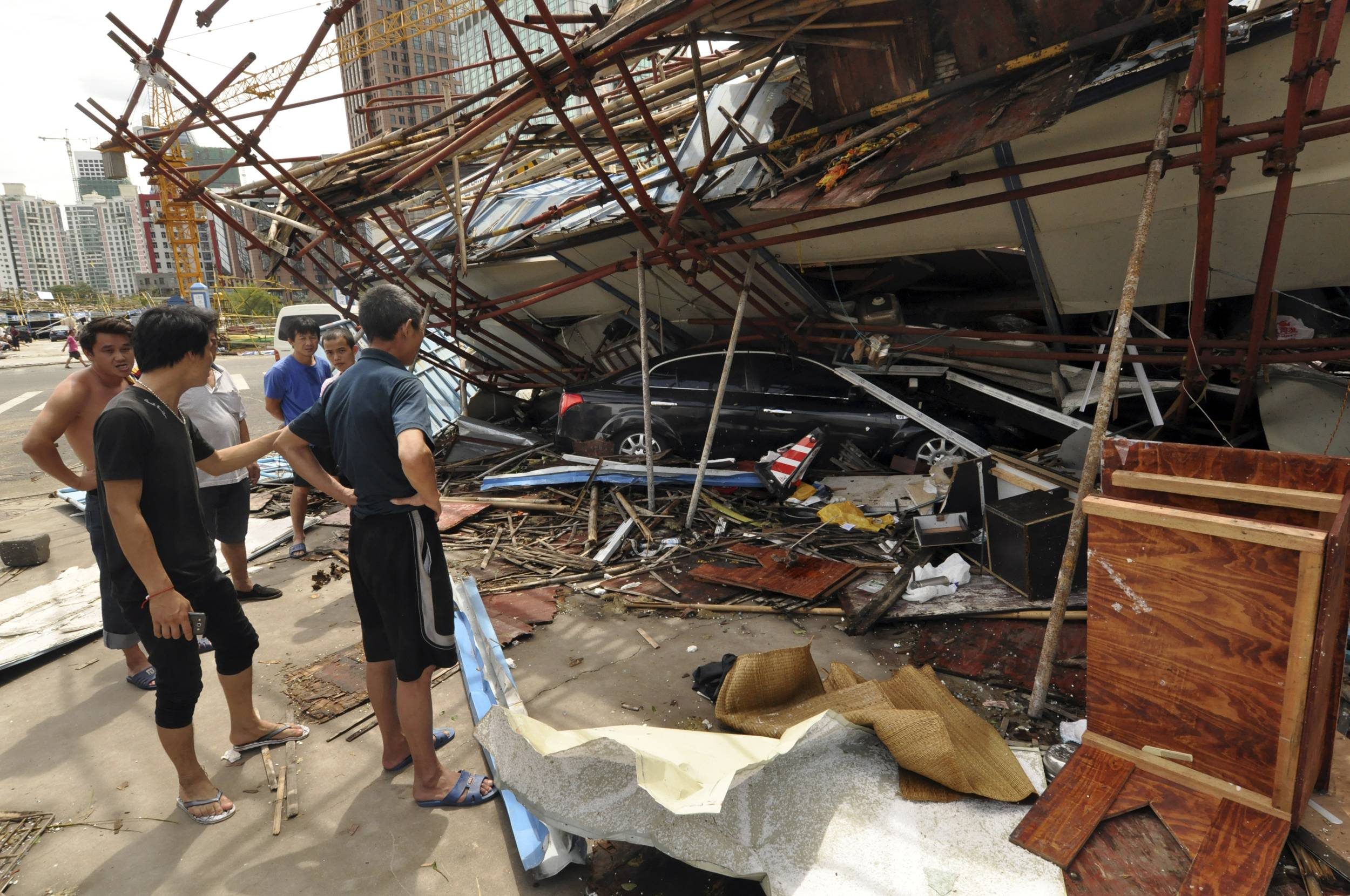 In this Saturday, July 19, 2014 photo released by China's Xinhua News Agency, a vehicle sits under a collapsed building after landfall of typhoon Rammasun in Haikou, capital of south China's Hainan Province. The strongest typhoon to hit southern China in four decades has killed more than a dozen people, the government said Sunday.