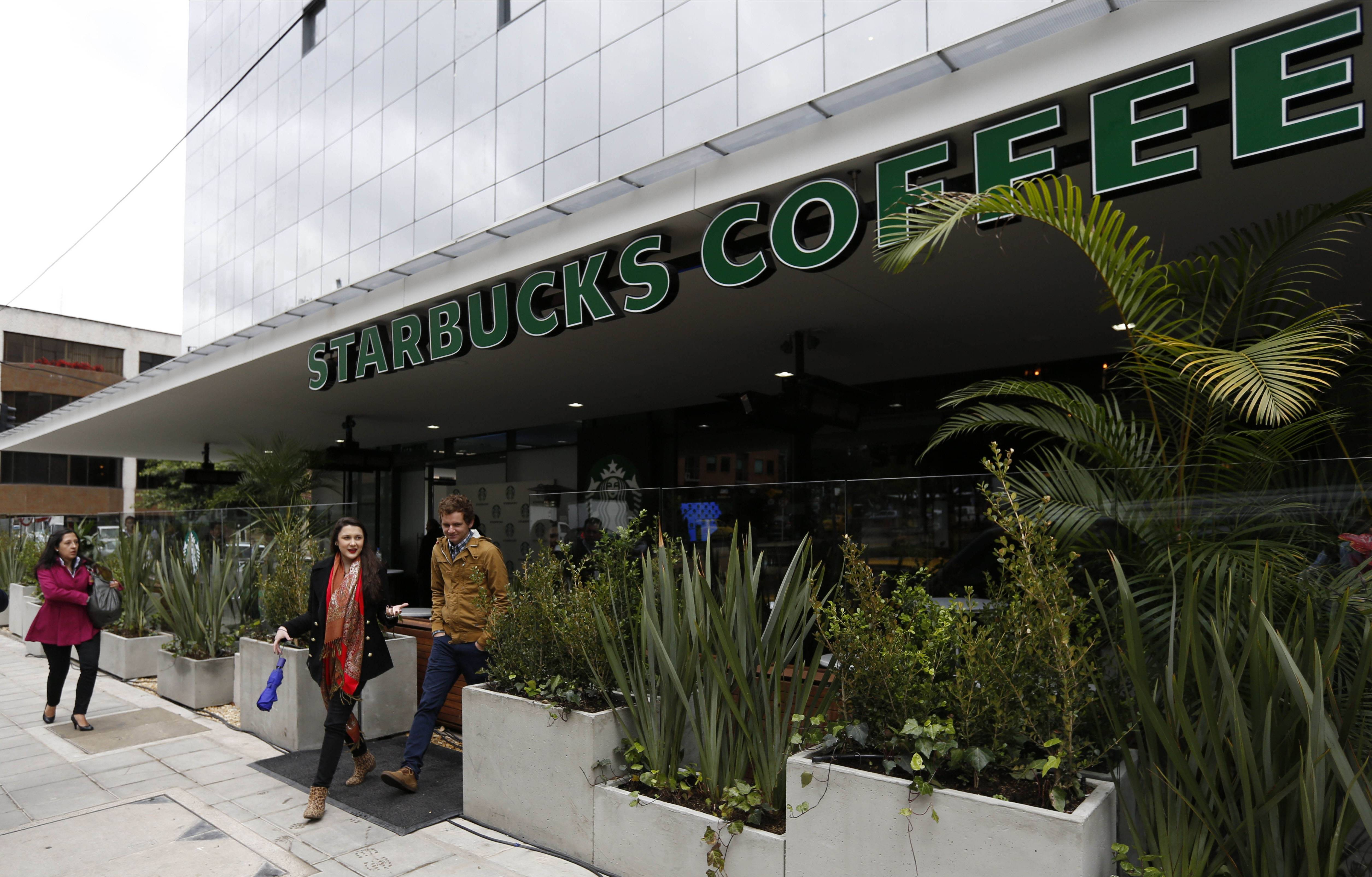 People walk past the first Starbucks to open in Bogota, Colombia, Wednesday, July 16, 2014. The three-floor coffee house in Bogota is the first of 50 that the Seattle-based company plans to open here in the next five years.