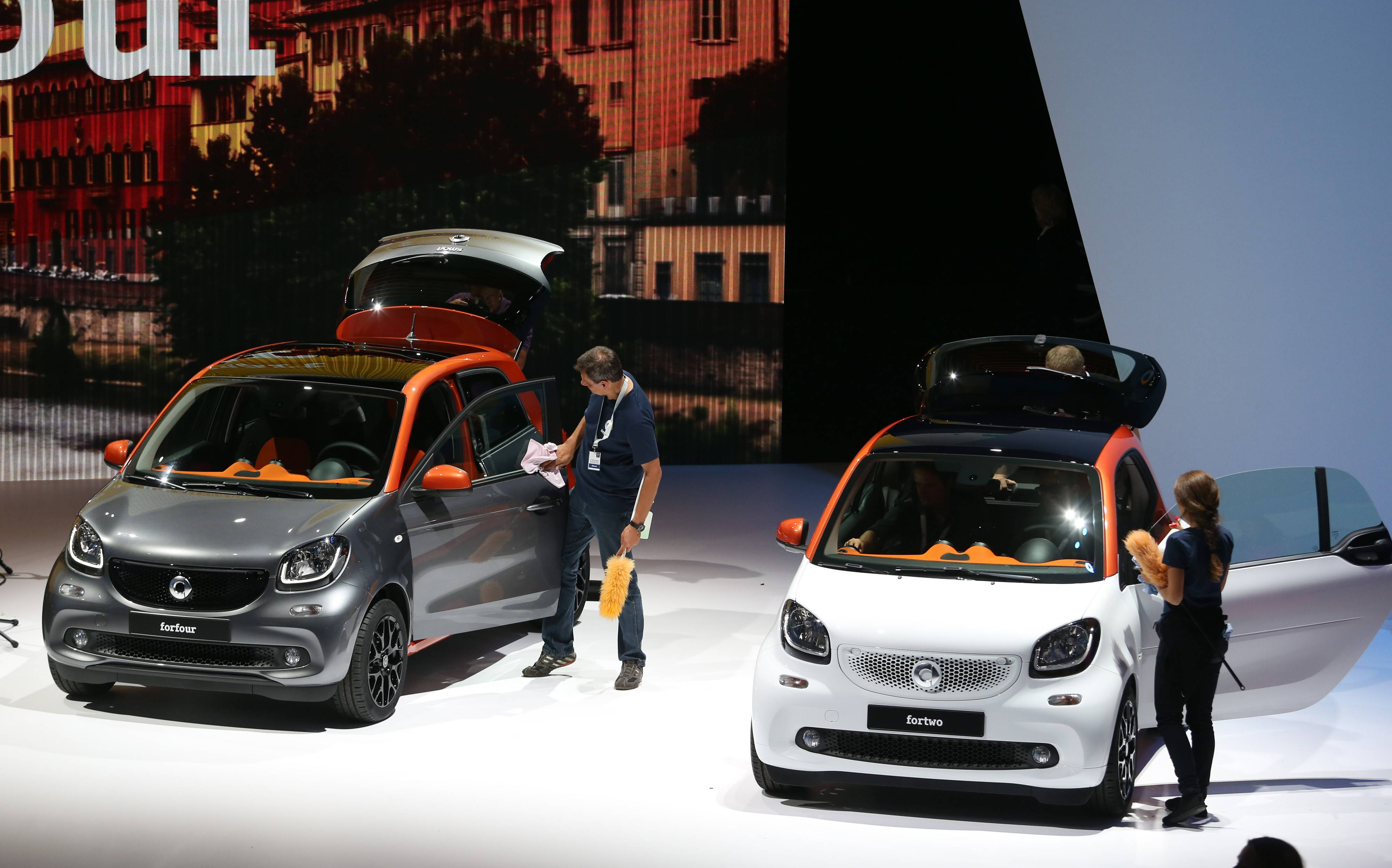 Employees clean a Smart ForTwo and a Smart ForFour electric automobile, manufactured by Daimler AG, at the car's world premiere in Berlin, Germany. Daimler's Smart brand unveiled a new version of its two-seat city car and revived a four-seat model as the sister division of luxury-vehicle maker Mercedes-Benz resumes a push to attract urban buyers.