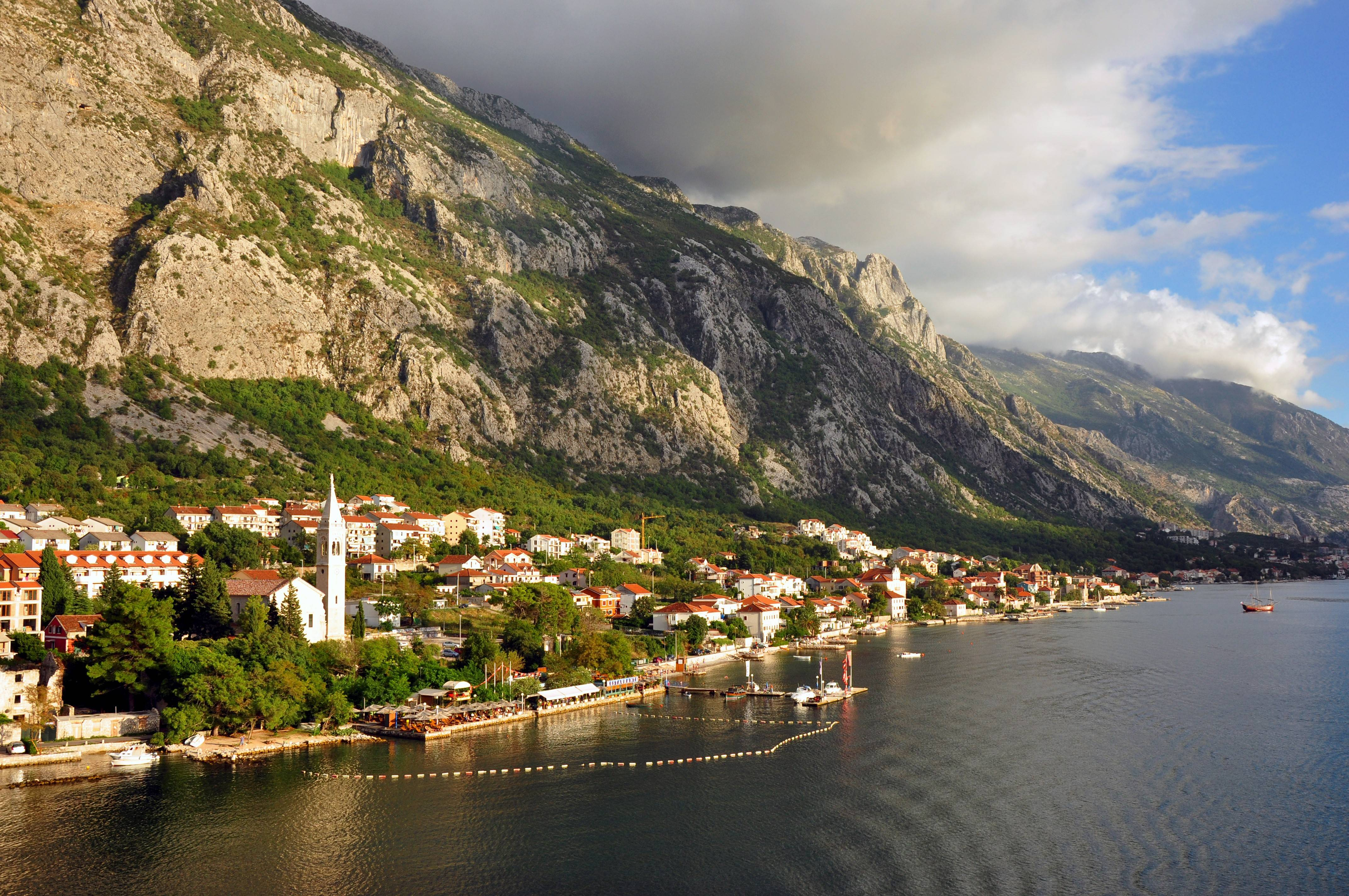 The Bay of Kotor in Montenegro is one of the longest inlets on the Dalmatian Coast. Villages of stone buildings with red roofs dot the shoreline.