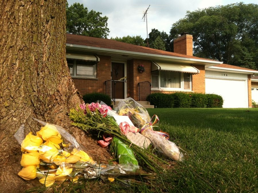 "Flowers and cards placed at the base of a tree in front of the home of Mildred ""Dodie"" Darrington serve as a memorial to the 85-year-old woman, who police say was stabbed to death Friday night."