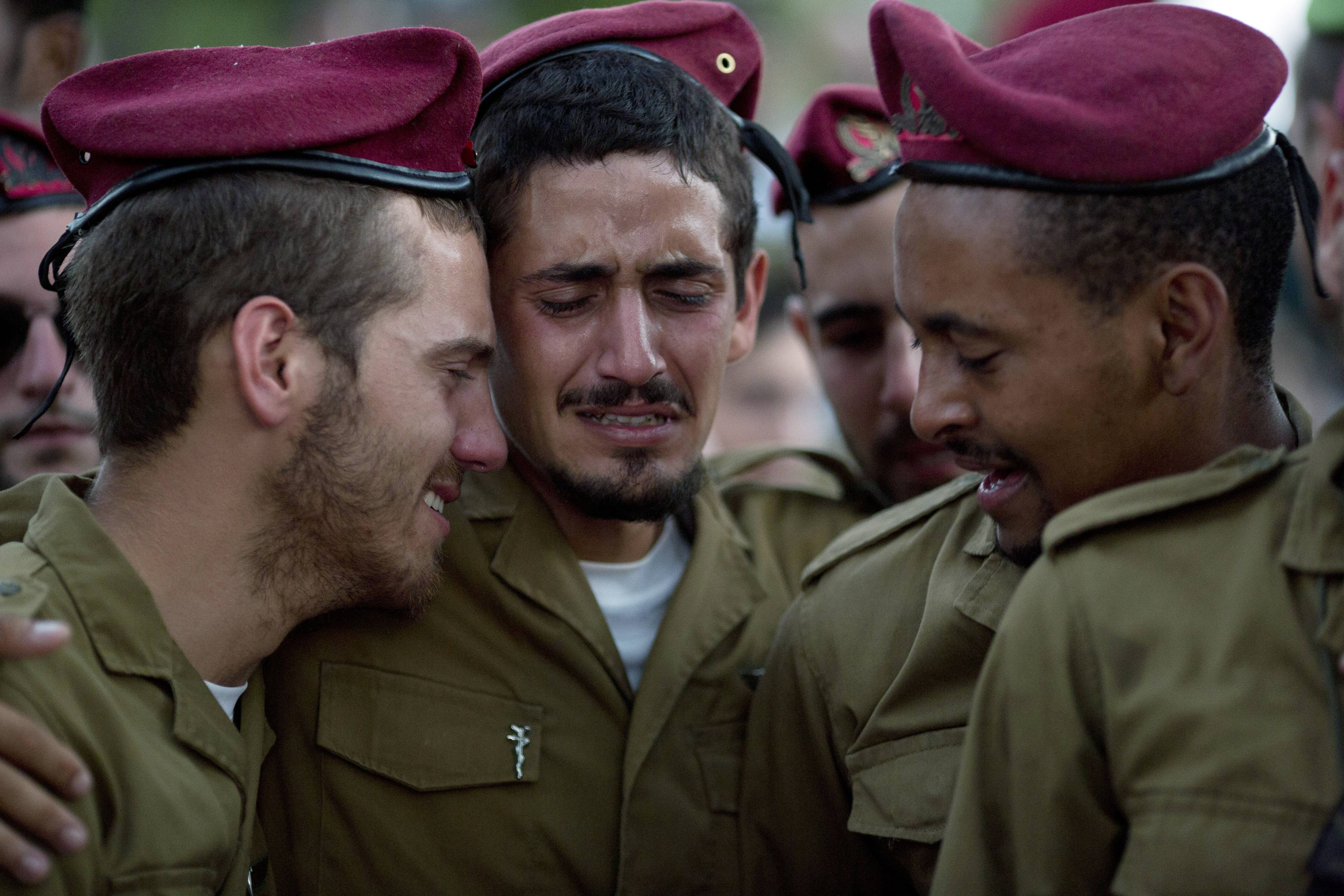 Israeli soldiers mourn over the grave of Sgt. Bnaya Rubel during his funeral at the military cemetery in Holon, Israel, Sunday. Rubel was killed while fighting Palestinian militants in Gaza on Saturday.