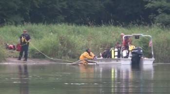 In this image taken from video, divers search the Fox River near Carpentersville on Sunday after a swimmer went missing.