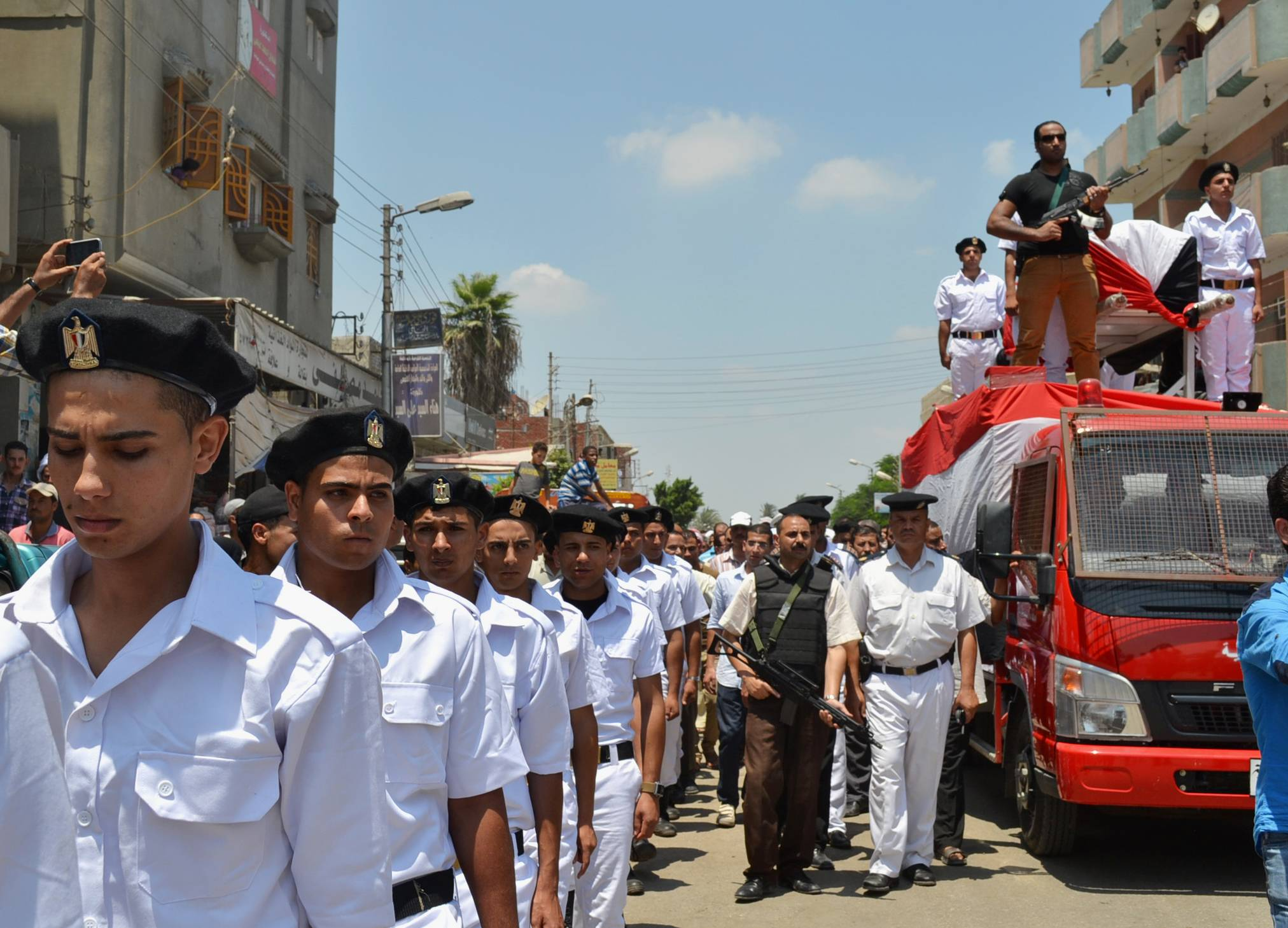 Members of the Egyptian security forces attend the funeral for a police officer who was killed by unknown gunmen Friday, while marching on a street in Abou Khalifa in the Ismailia governorate, 120 kilometers (75 miles) east of Cairo, Egypt, Saturday, July 19, 2014. According to officials, the officer was shot dead by unknown gunmen in el-Arish, a city in the Sinai, where Egypt is fighting Islamic extremists. (