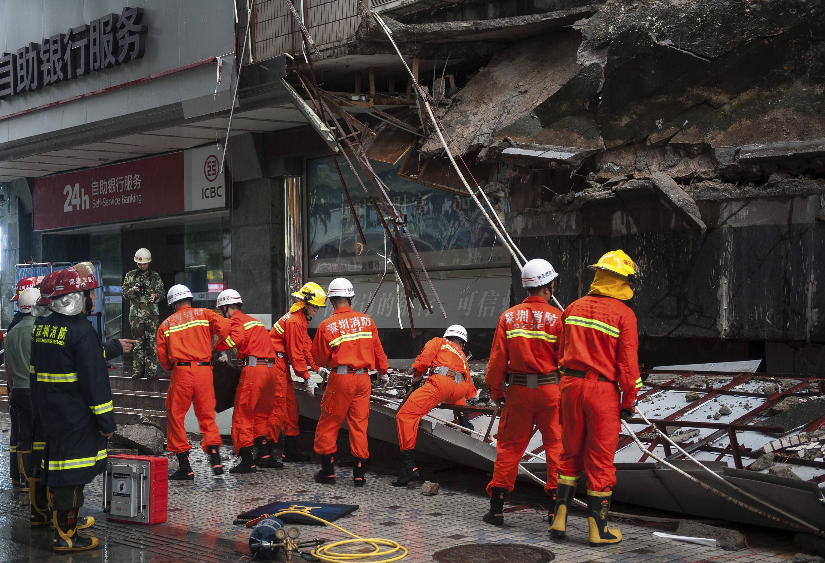 Rescuers try to remove a steal frame from a collapsed concrete roof which has killed and injured a number of people after they took shelter during heavy rains in Shenzhen in south China's Guangdong province Friday, July 18, 2014. A powerful typhoon hit the southern Chinese island of Hainan on Friday after killing tens people in the Philippines.