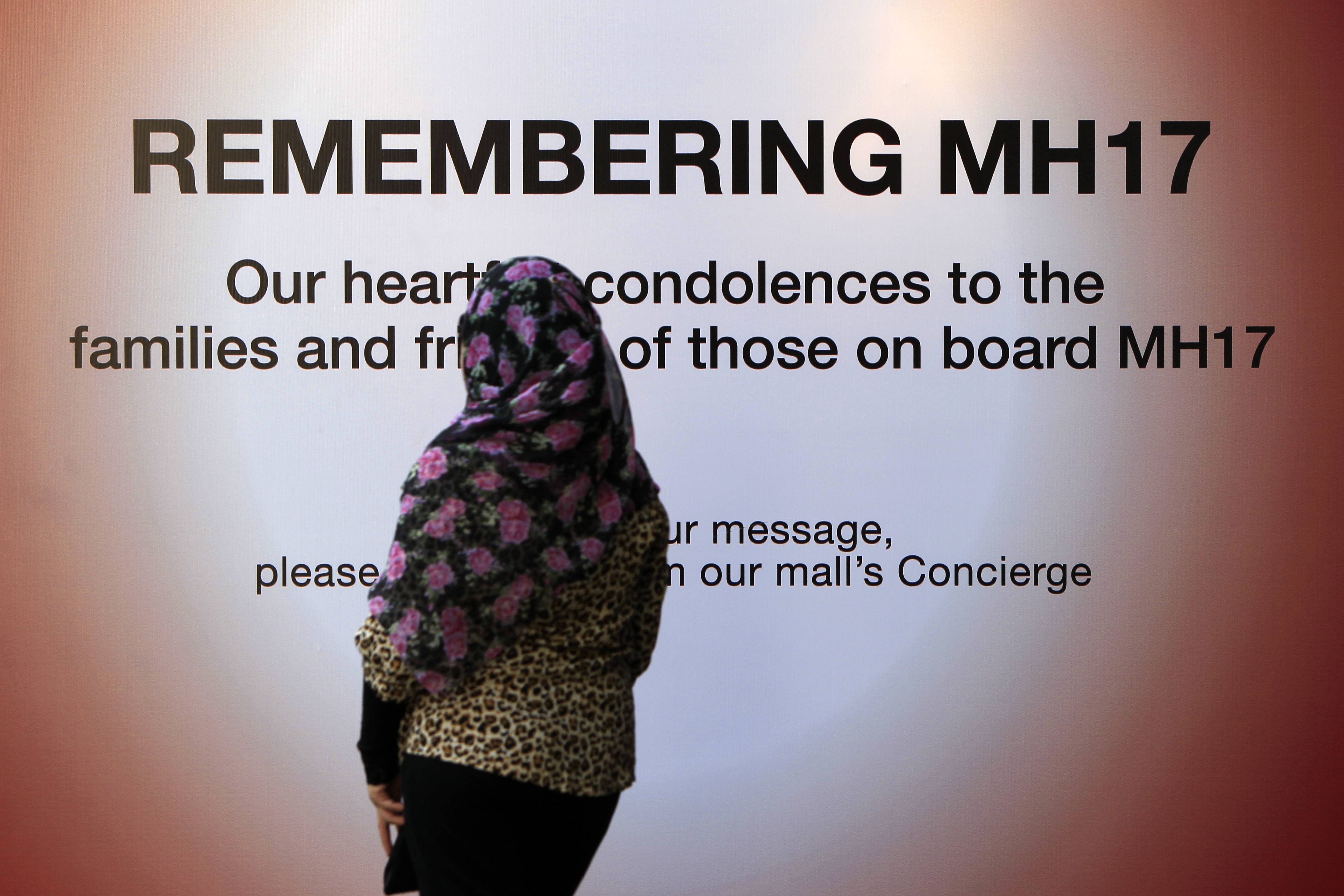 A woman walks past a message board for victims of the crashed Malaysia Airlines Flight 17, at a shopping mall in Kuala Lumpur, Malaysia, Sunday, July 20, 2014. Separatist rebels in Ukraine have recovered the black boxes from the downed Malaysia Airlines Flight 17 and will hand them over to the International Civil Aviation Organization, a rebel leader said Sunday.