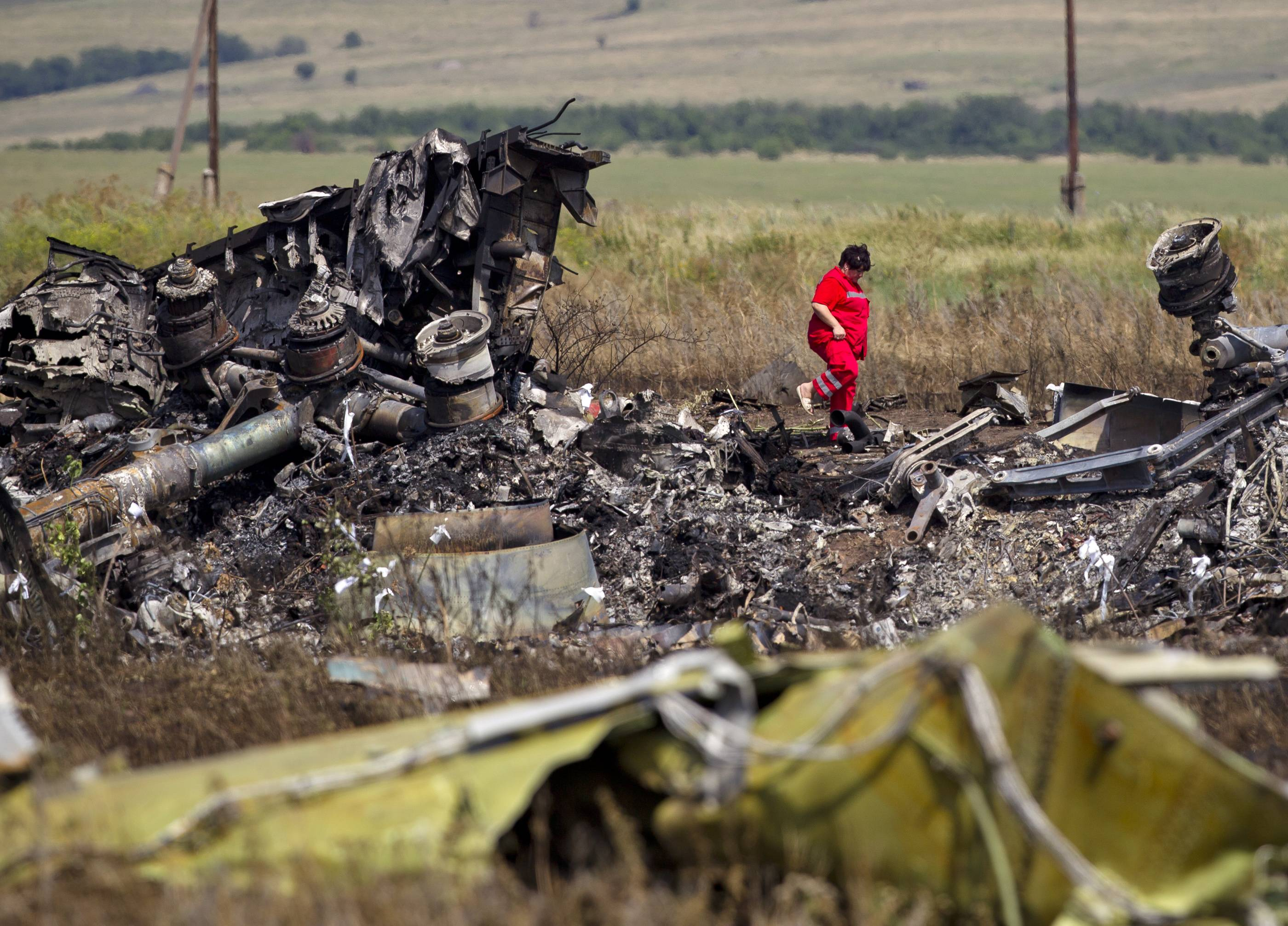 An Ukrainian paramedic walks amongst charred debris at the crash site of Malaysia Airlines Flight 17 near the village of Hrabove, eastern Ukraine, Sunday. Armed rebels forced emergency workers to hand over all 196 bodies recovered from the Malaysia Airlines crash site and had them loaded Sunday onto refrigerated train cars bound for a rebel-held city, Ukrainian officials and monitors said.