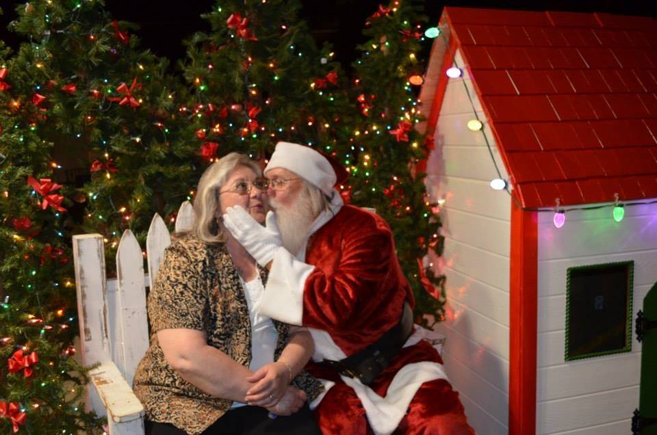 Santa Paul Eggert gives a smooch to his wife, Giuliana, during a previous Christmas in July celebration at the Banana Split ice cream parlor in Aurora.