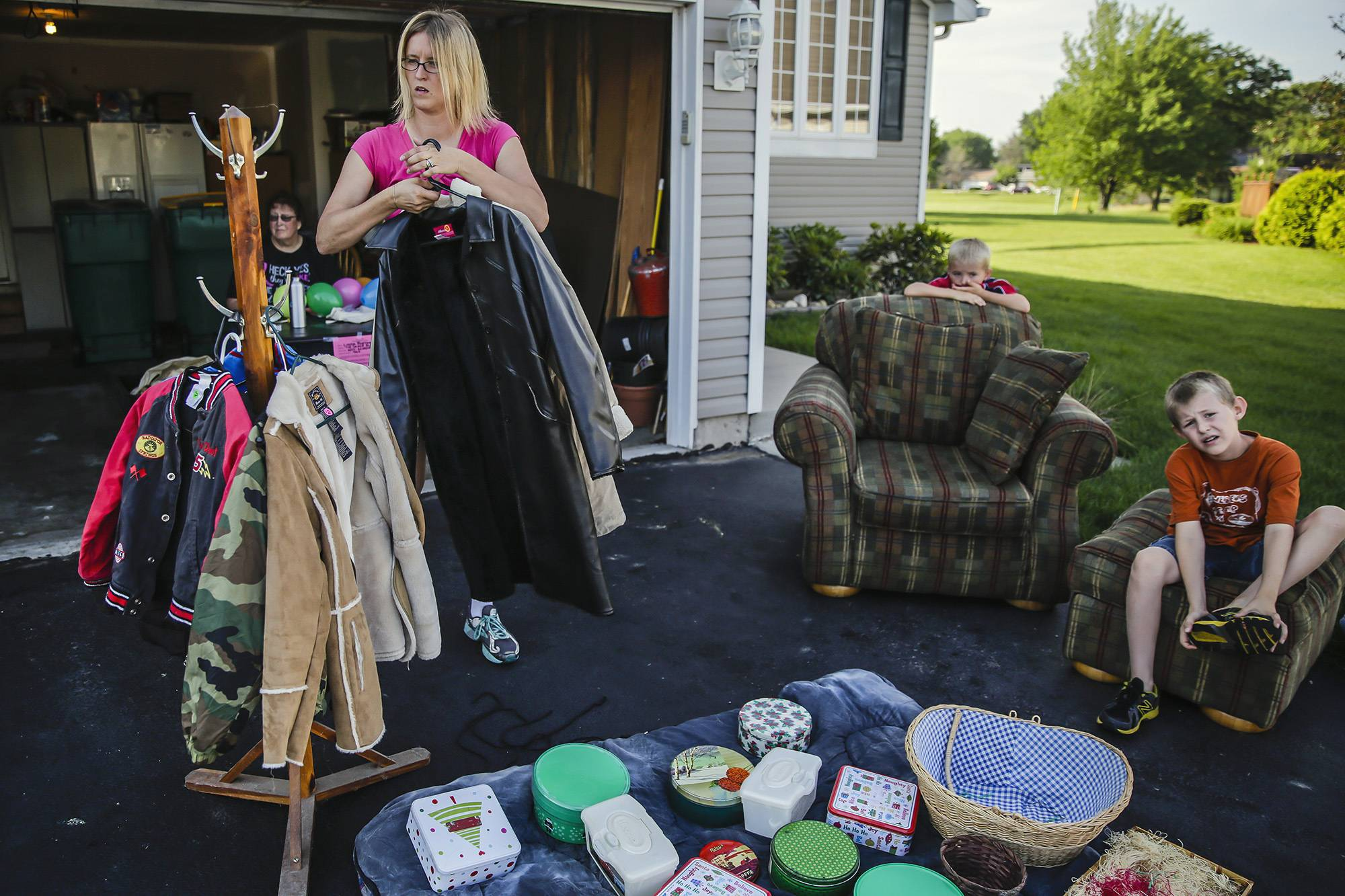Heidi Cole hangs coats on a coat rack as she prepares for a garage sale at her mother Linda Burton's home in Joliet. The sale had some furniture, kids' toys, electronics and household items like silverware and glasses, including an old desktop computer and a toaster oven.